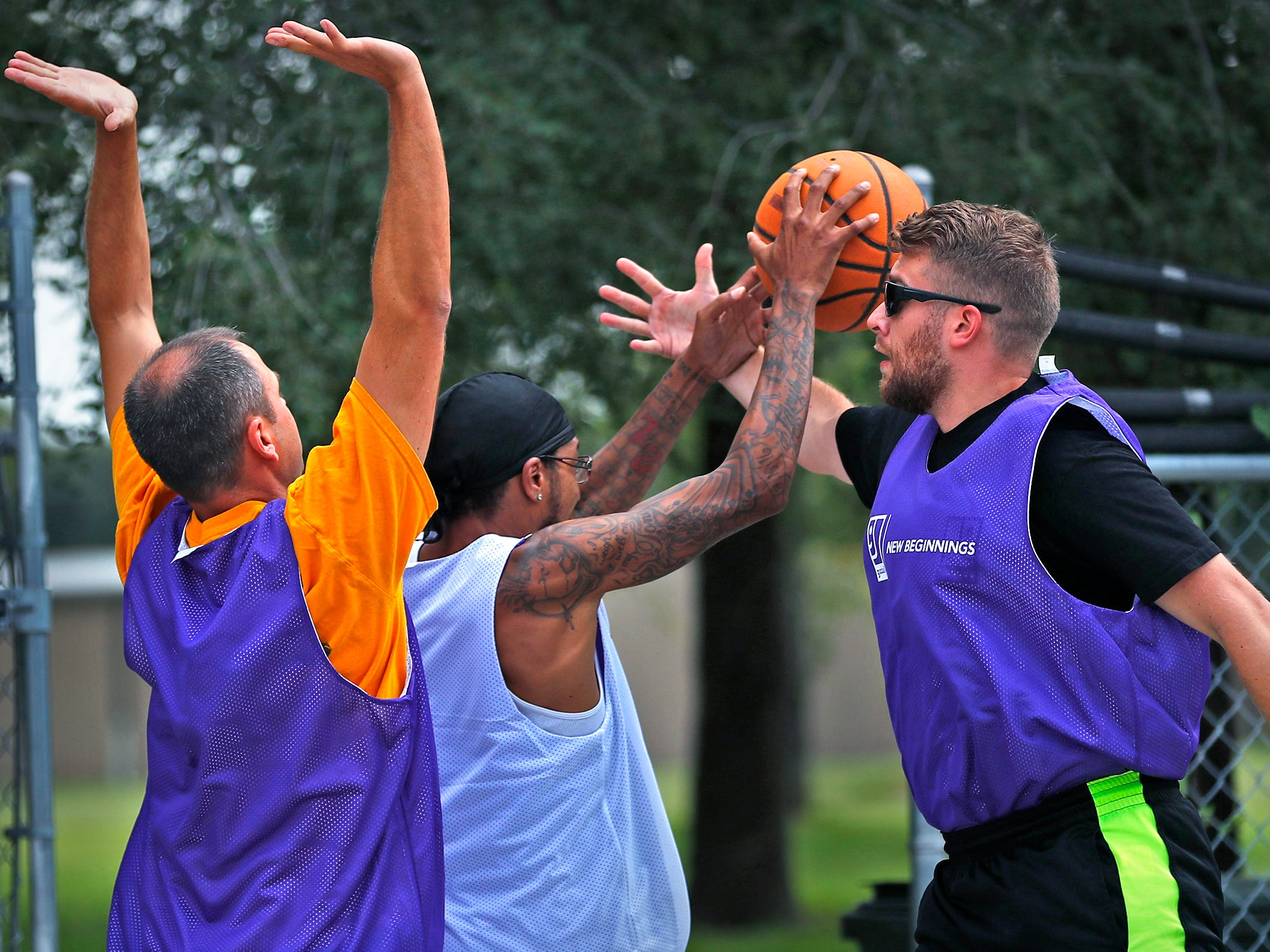 Eric Schlegel, Vice President for Goodwill Southern and Central Indiana Retail Division, from left, Michael Patrick, New Beginnings participant, and Austin Paschal, with Marion County Probations, battle during a basketball game at Goodwill Commercial Services, Wednesday, Sept. 19, 2018.  Goodwill Industries of Central Indiana's New Beginnings hosted the 3-on-3 basketball tournament bringing together participants in New Beginnings, a six-month re-entry program for ex-offenders that works on job and life skills, with representatives from Goodwill, IMPD, the Mayor's office, Marion County Probation department and other services.  The goal is to celebrate the New Beginnings program while breaking down re-entry barriers through basketball.