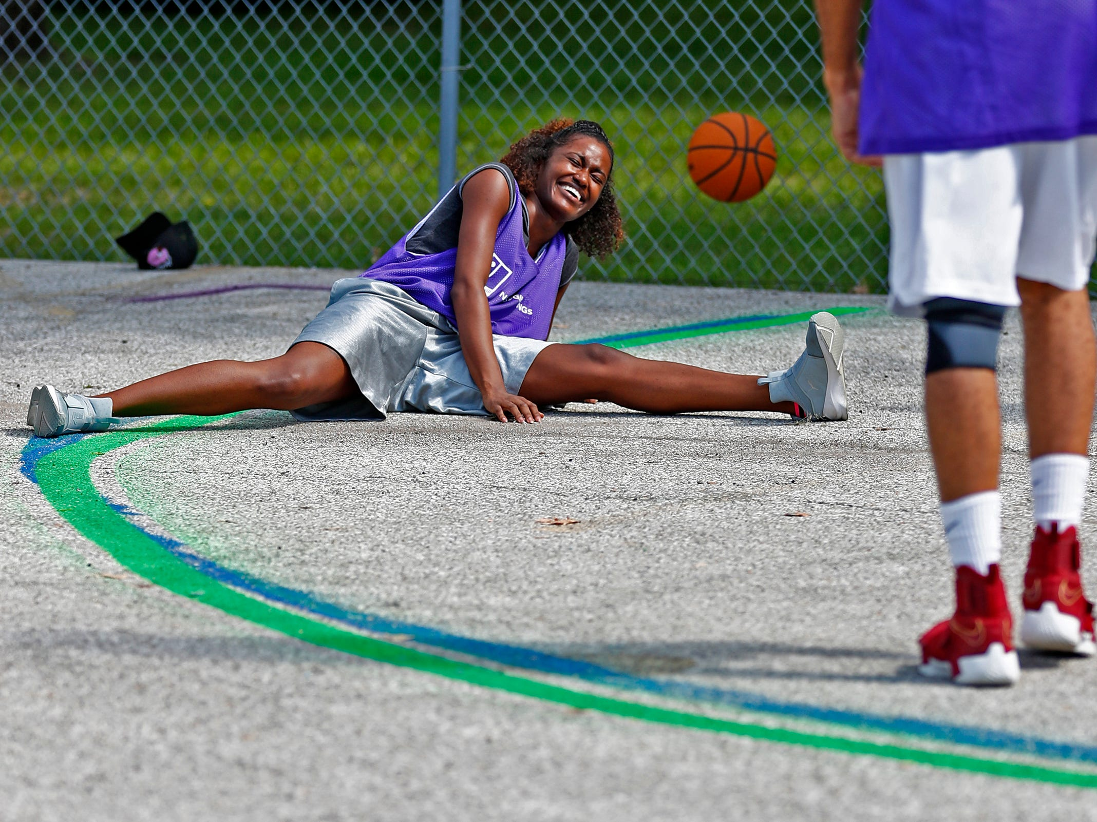 Alexaundria Monroe, with Marion County Probations, laughs as she fell into a spilt, during a basketball game at Goodwill Commercial Services, Wednesday, Sept. 19, 2018.  Goodwill Industries of Central Indiana's New Beginnings hosted the 3-on-3 basketball tournament bringing together participants in New Beginnings, a six-month re-entry program for ex-offenders that works on job and life skills, with representatives from Goodwill, IMPD, the Mayor's office, Marion County Probation department and other services.  The goal is to celebrate the New Beginnings program while breaking down re-entry barriers through basketball.
