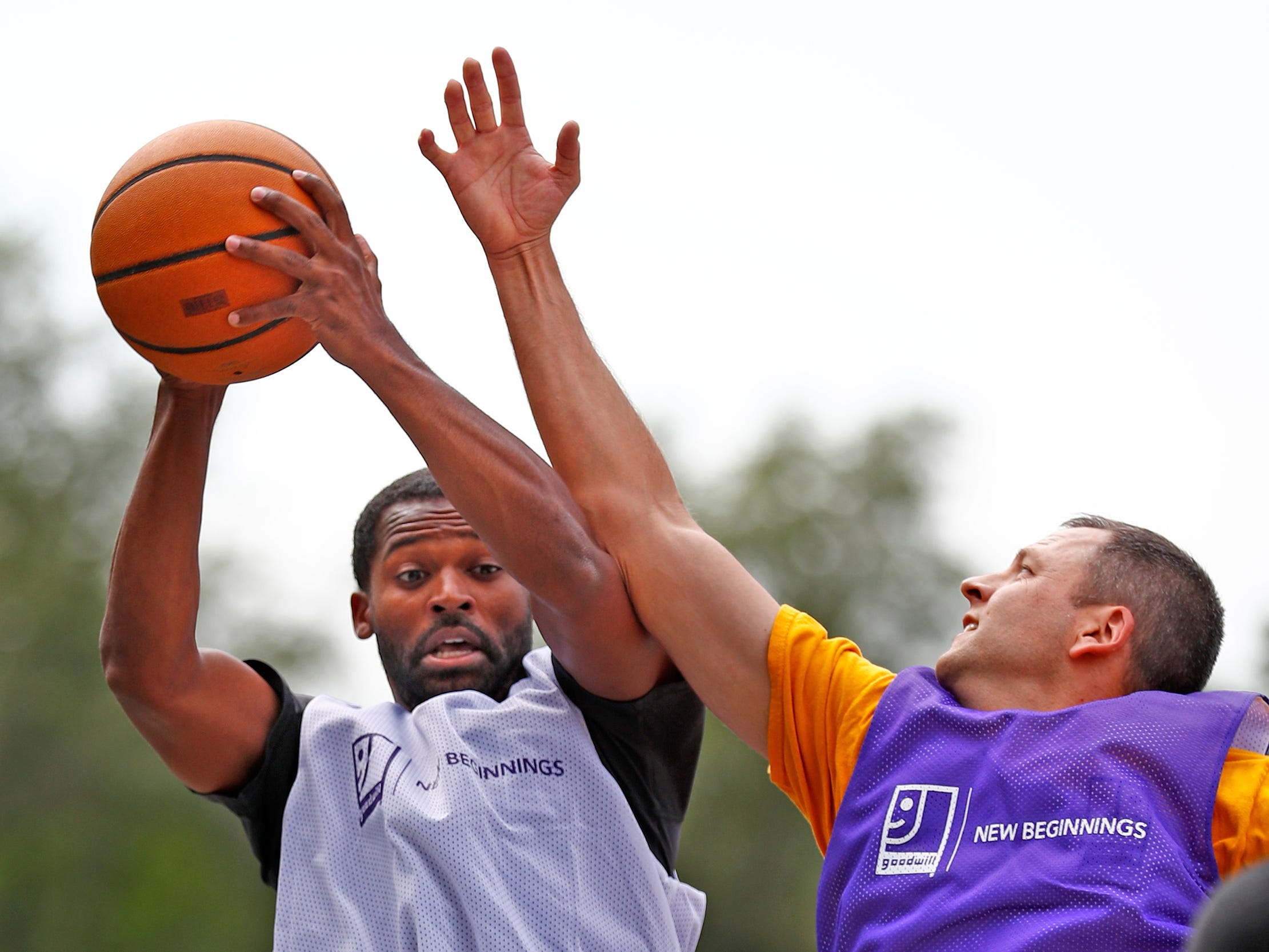 Taylor Hopkins, with Goodwill Guides, shoots past Eric Schlegel, Vice President for Goodwill Southern and Central Indiana Retail Division, during a basketball game at Goodwill Commercial Services, Wednesday, Sept. 19, 2018.  Goodwill Industries of Central Indiana's New Beginnings hosted the 3-on-3 basketball tournament bringing together participants in New Beginnings, a six-month re-entry program for ex-offenders that works on job and life skills, with representatives from Goodwill, IMPD, the Mayor's office, Marion County Probation department and other services.  The goal is to celebrate the New Beginnings program while breaking down re-entry barriers through basketball.