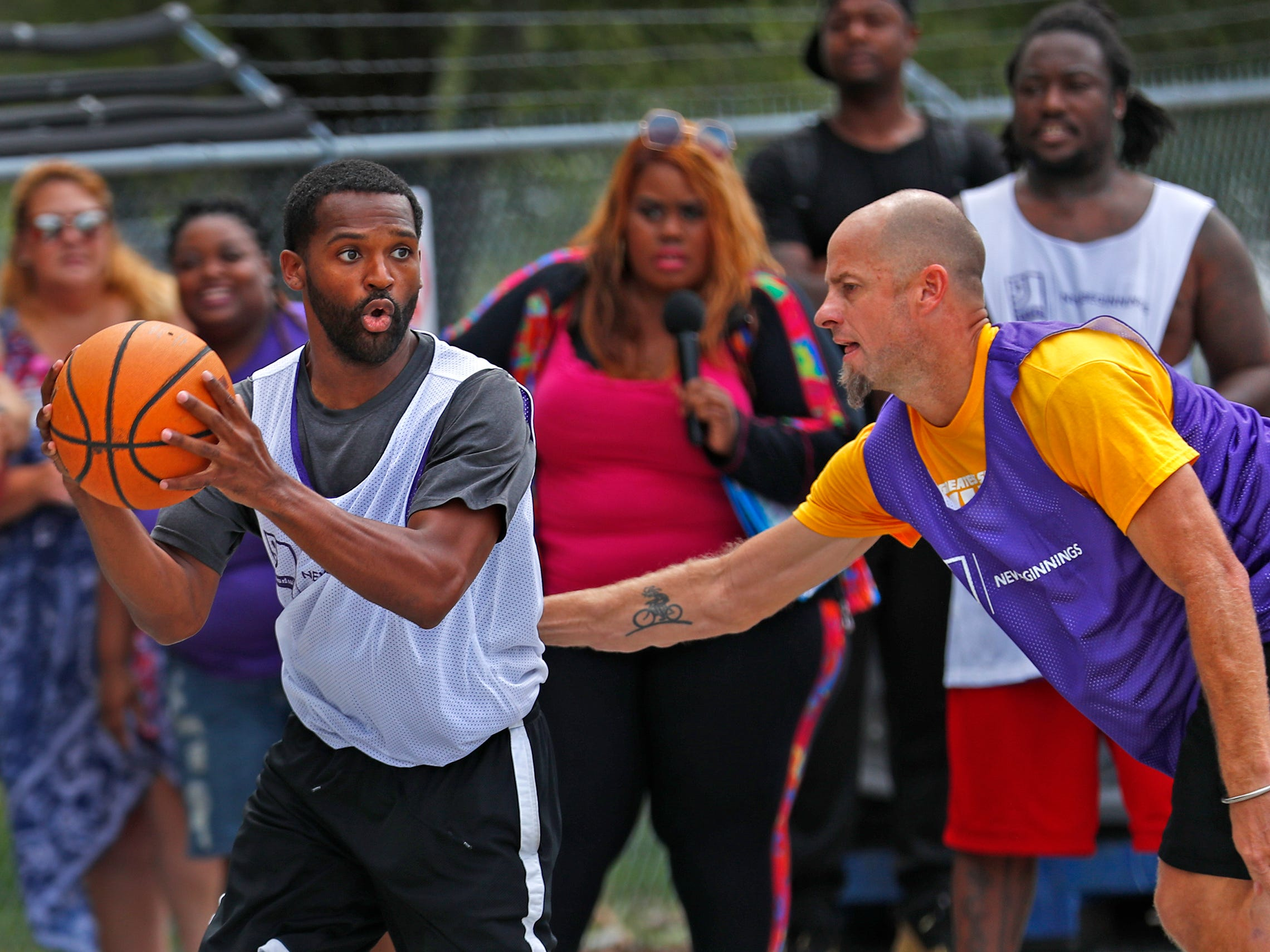 Taylor Hopkins, with Goodwill Guides, moves past Roger Hasper, with Goodwill, during a basketball game at Goodwill Commercial Services, Wednesday, Sept. 19, 2018.  Goodwill Industries of Central Indiana's New Beginnings hosted the 3-on-3 basketball tournament bringing together participants in New Beginnings, a six-month re-entry program for ex-offenders that works on job and life skills, with representatives from Goodwill, IMPD, the Mayor's office, Marion County Probation department and other services.  The goal is to celebrate the New Beginnings program while breaking down re-entry barriers through basketball.