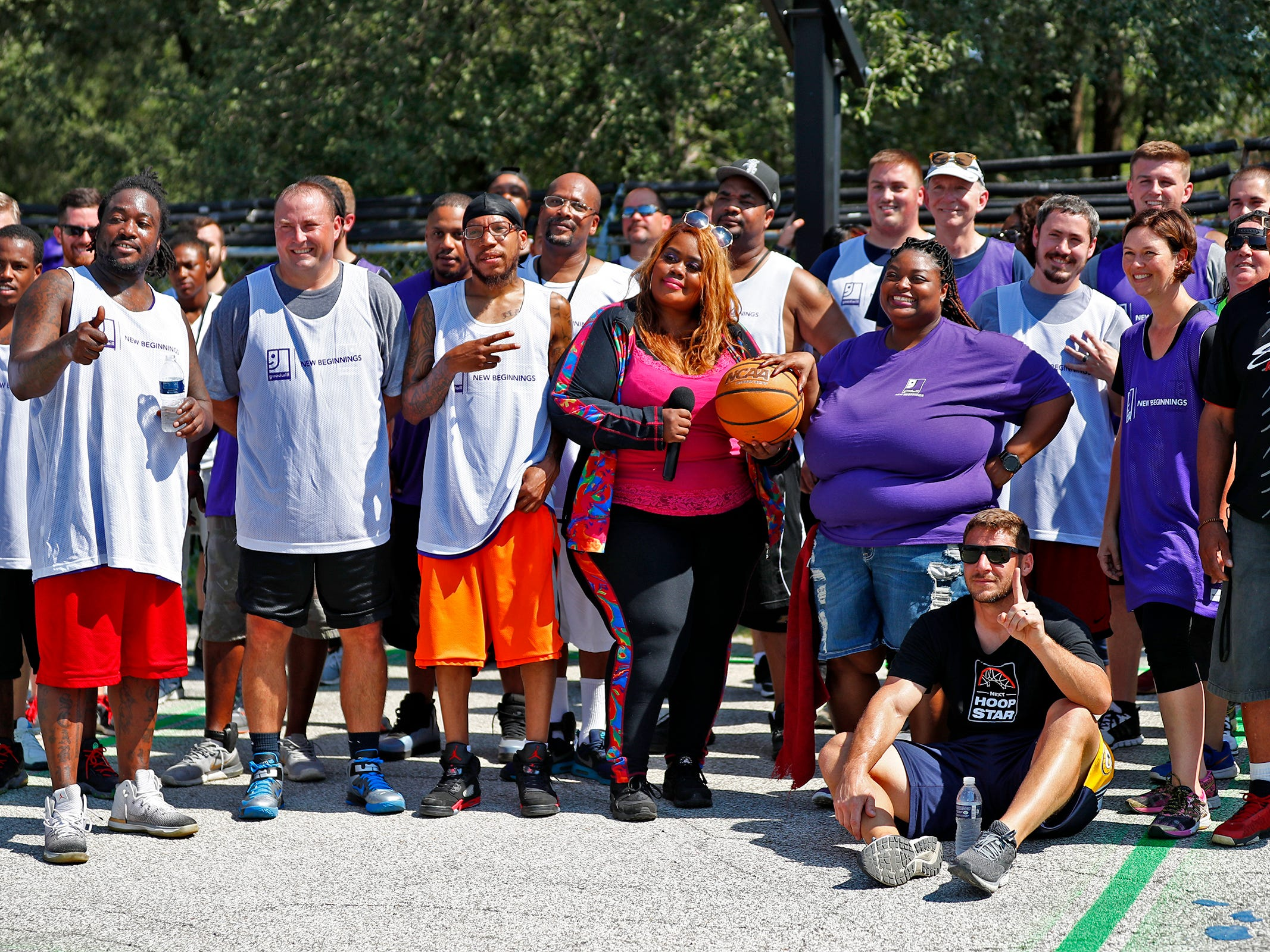 People gather for a group photo after 3-on-3 basketball games at Goodwill Commercial Services, Wednesday, Sept. 19, 2018.  Goodwill Industries of Central Indiana's New Beginnings hosted the 3-on-3 basketball tournament bringing together participants in New Beginnings, a six-month re-entry program for ex-offenders that works on job and life skills, with representatives from Goodwill, IMPD, the Mayor's office, Marion County Probation department and other services.  The goal is to celebrate the New Beginnings program while breaking down re-entry barriers through basketball.
