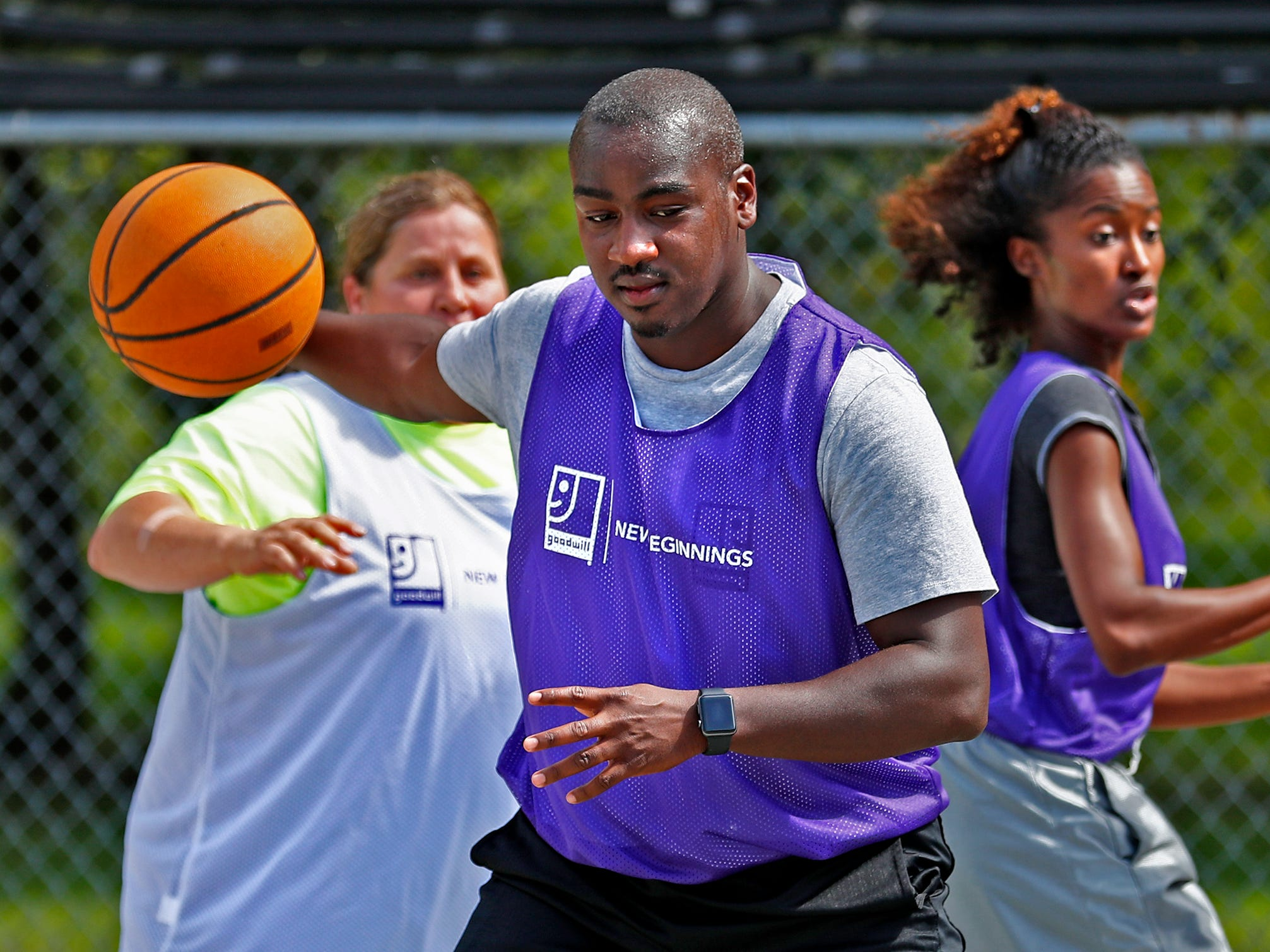 Kevin Tichenor, with Family Community Partners, runs the ball past Tonya Surber, left, Alexaundria Monroe, both with Marion County Probations, during a basketball game at Goodwill Commercial Services, Wednesday, Sept. 19, 2018.  Goodwill Industries of Central Indiana's New Beginnings hosted the 3-on-3 basketball tournament bringing together participants in New Beginnings, a six-month re-entry program for ex-offenders that works on job and life skills, with representatives from Goodwill, IMPD, the Mayor's office, Marion County Probation department and other services.  The goal is to celebrate the New Beginnings program while breaking down re-entry barriers through basketball.