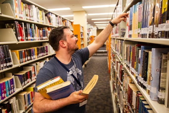 Steve Long, a University of Iowa senior, of Marion stocks shelves in the fiction section on Wednesday, Sept. 19, 2018, at the Iowa City Public Library. Long is studying informatics in the computer science department at the university and has worked at the public library for two years.