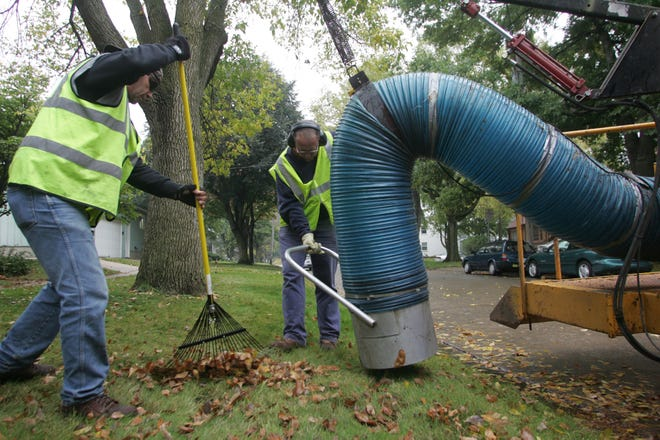 PC photo by Dan Williamson. 10-15-07. Iowa City employee Mark Prohosky, left, rakes leaves toward Pat Burns as they vacuum up leaves for the city's annual leaf-pickup service on Monday, Oct. 15, 2007. The service, which started Friday (Oct. 12), will continue through Nov. 22.