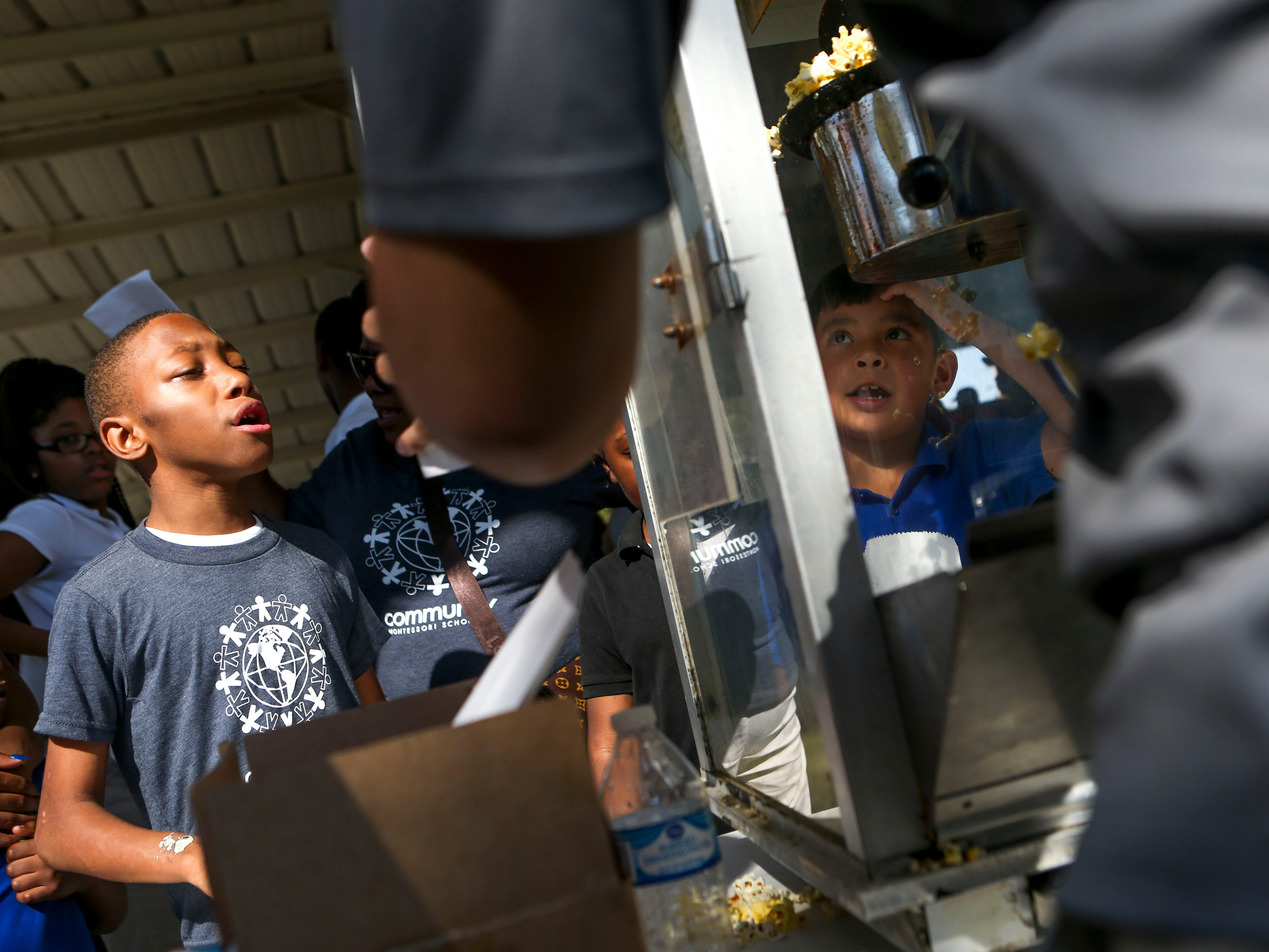 Kids wait in line for bags of popcorn at the Day of Champions celebration held at Jackson Fairgrounds Park in Jackson, Tenn., on Wednesday, Sept. 19, 2018.