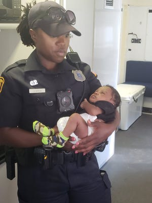 A Memphis Police Officer holds 3-week-old Stephen Smith, who was recovered safe after being allegedly abducted by his non-custodial father.