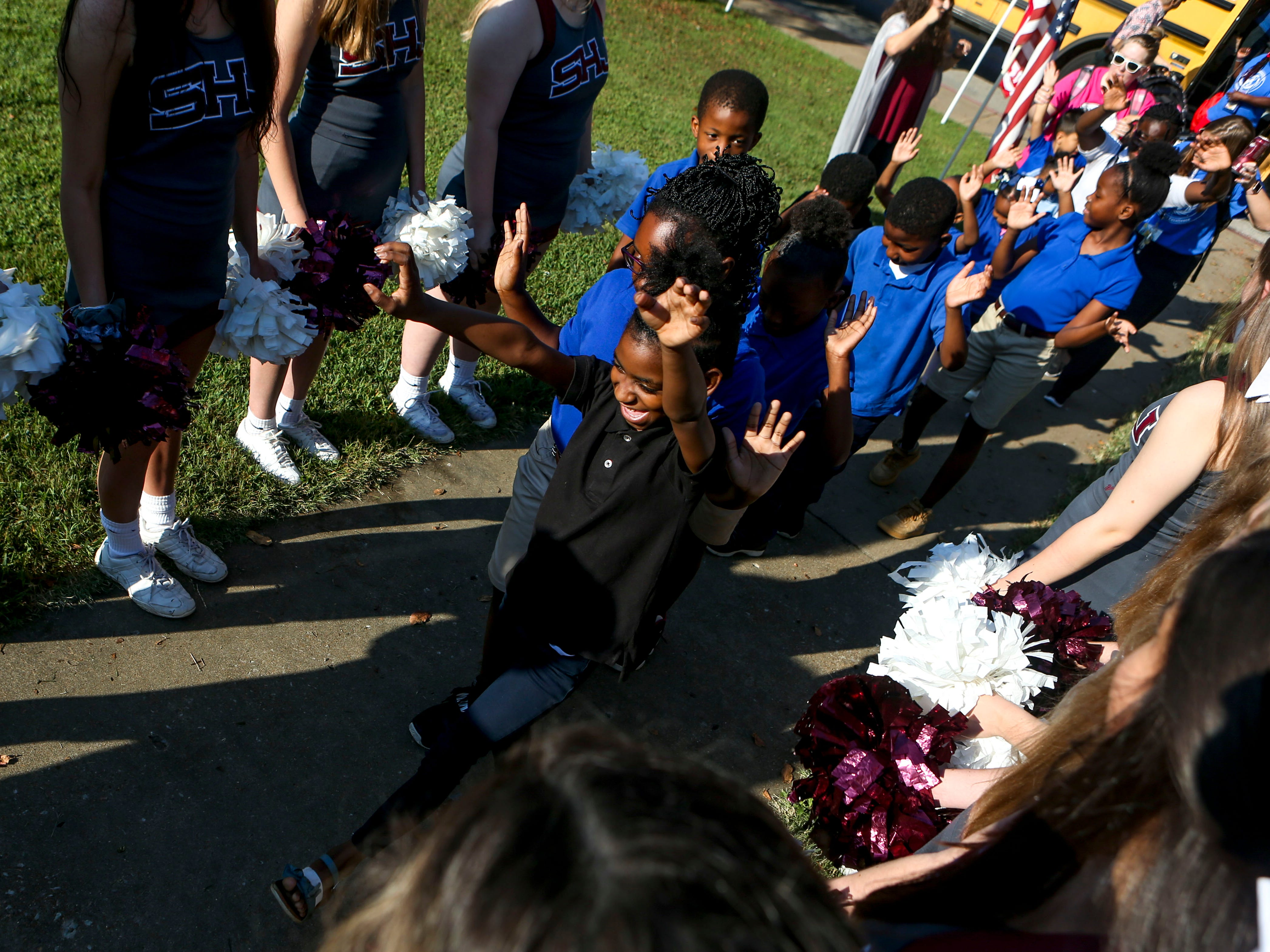 Attendees arrive to high fives from Sacred Heart cheerleaders and football players at the Day of Champions celebration held at Jackson Fairgrounds Park in Jackson, Tenn., on Wednesday, Sept. 19, 2018.