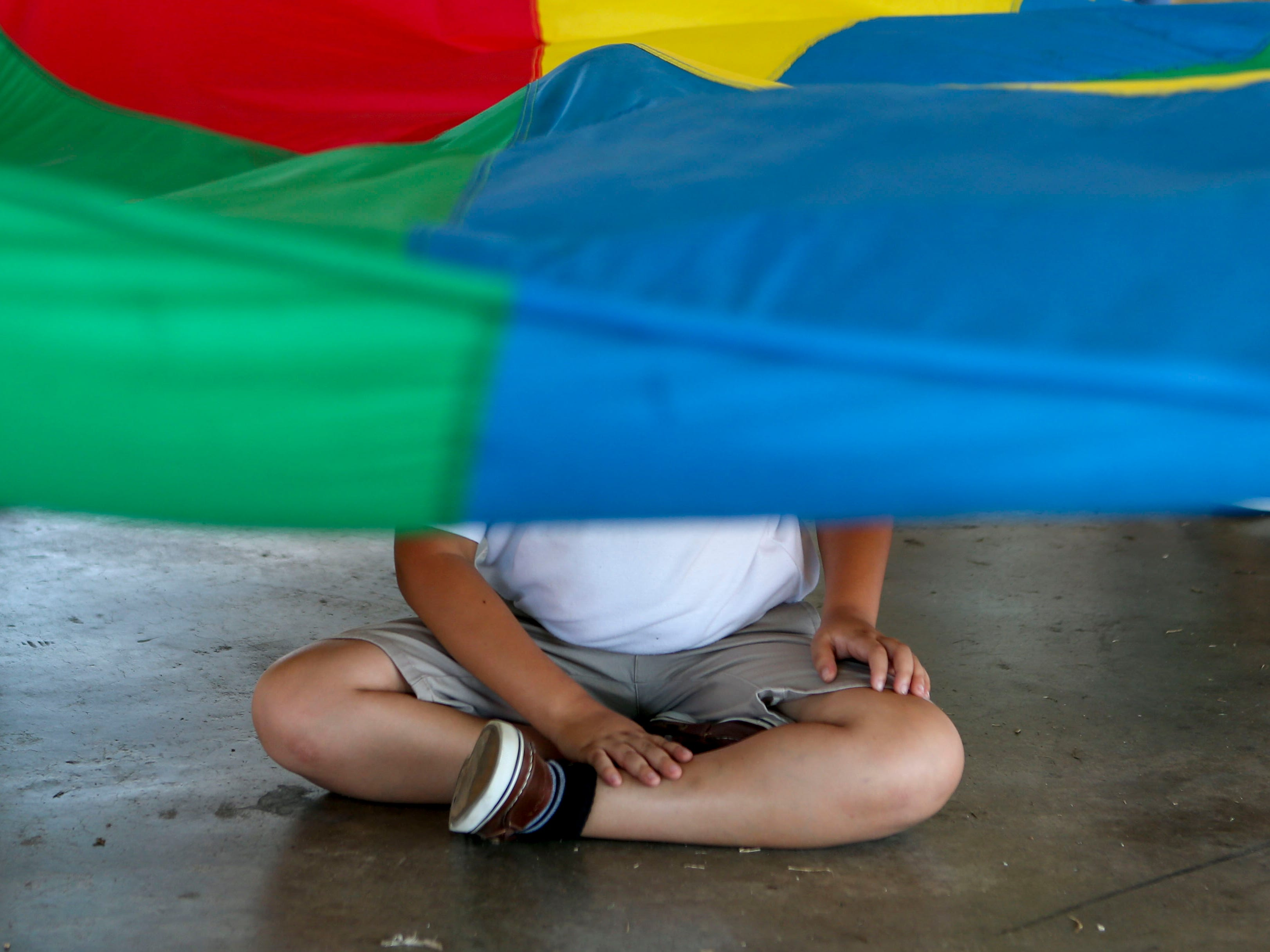 A young boy is shrouded by a tarp being tossed up and down by Sacred Heart students at the Day of Champions celebration held at Jackson Fairgrounds Park in Jackson, Tenn., on Wednesday, Sept. 19, 2018.