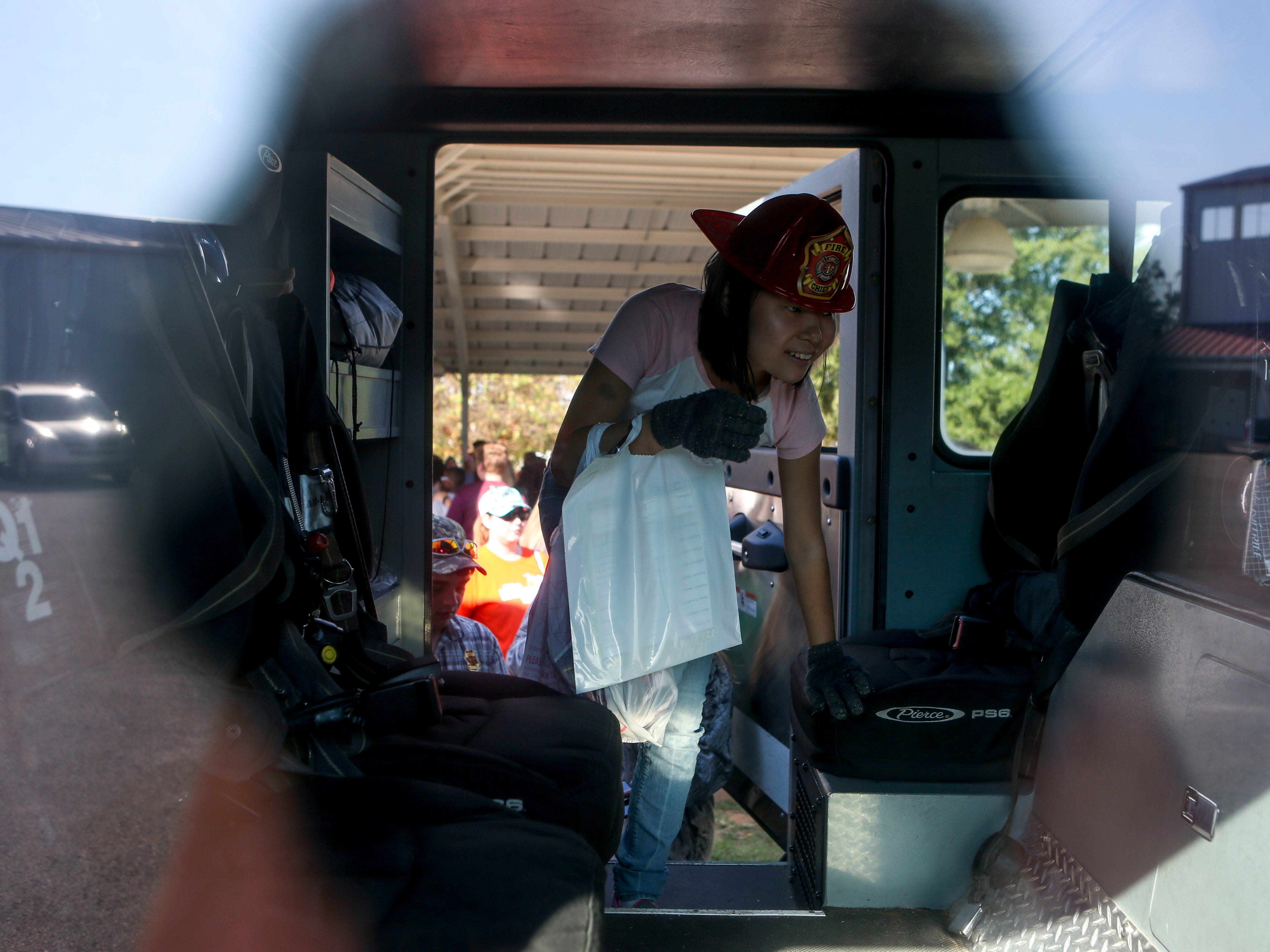 An attendee climbs into a firetruck that was brought out at the Day of Champions celebration held at Jackson Fairgrounds Park in Jackson, Tenn., on Wednesday, Sept. 19, 2018.