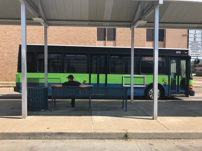 A man waits for his bus at the Jackson Transit Authority Transfer Center on E. Main Street in downtown Jackson.