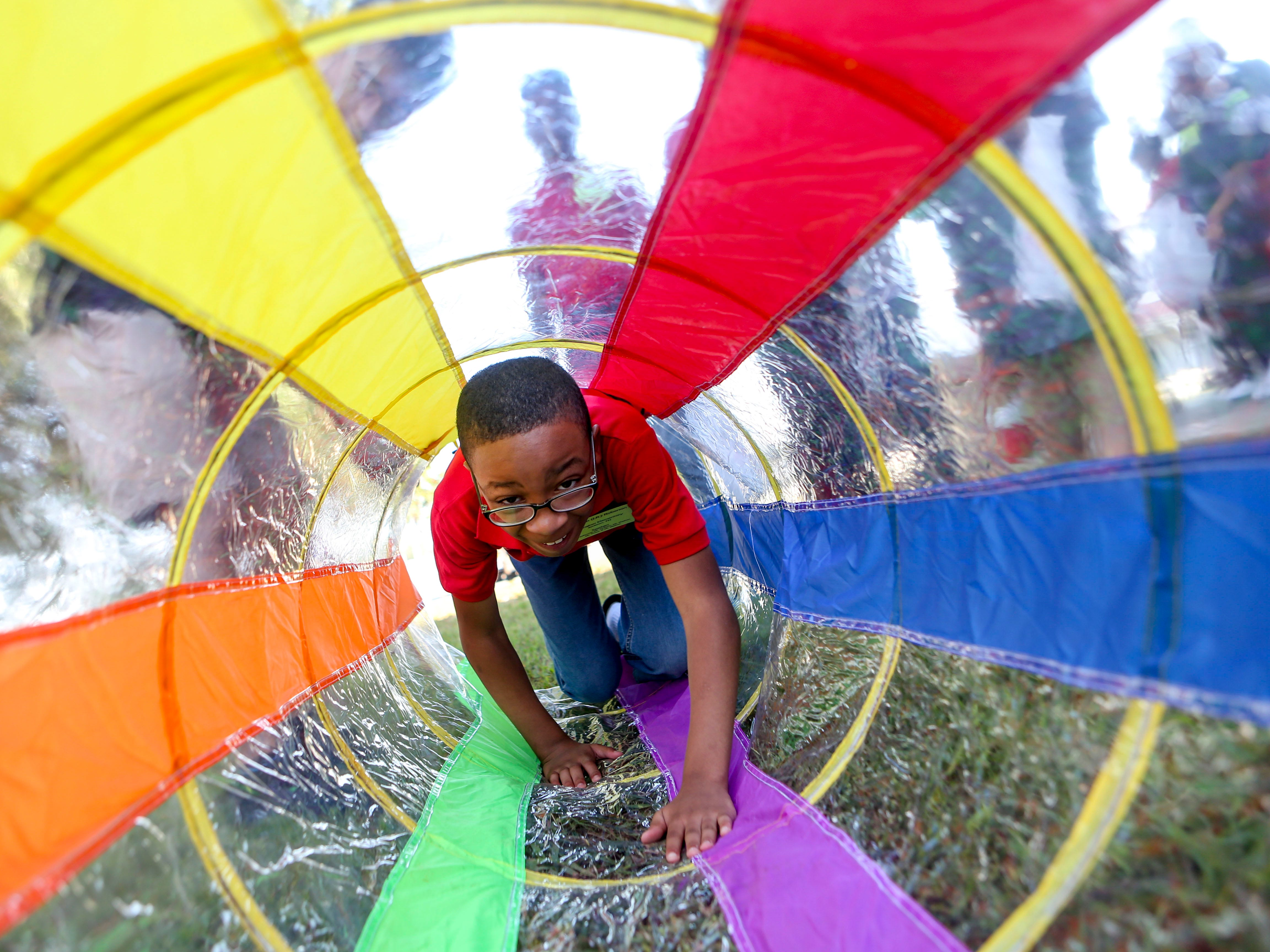 A young boy climbs through a small tunnel obstacle at the Day of Champions celebration held at Jackson Fairgrounds Park in Jackson, Tenn., on Wednesday, Sept. 19, 2018.
