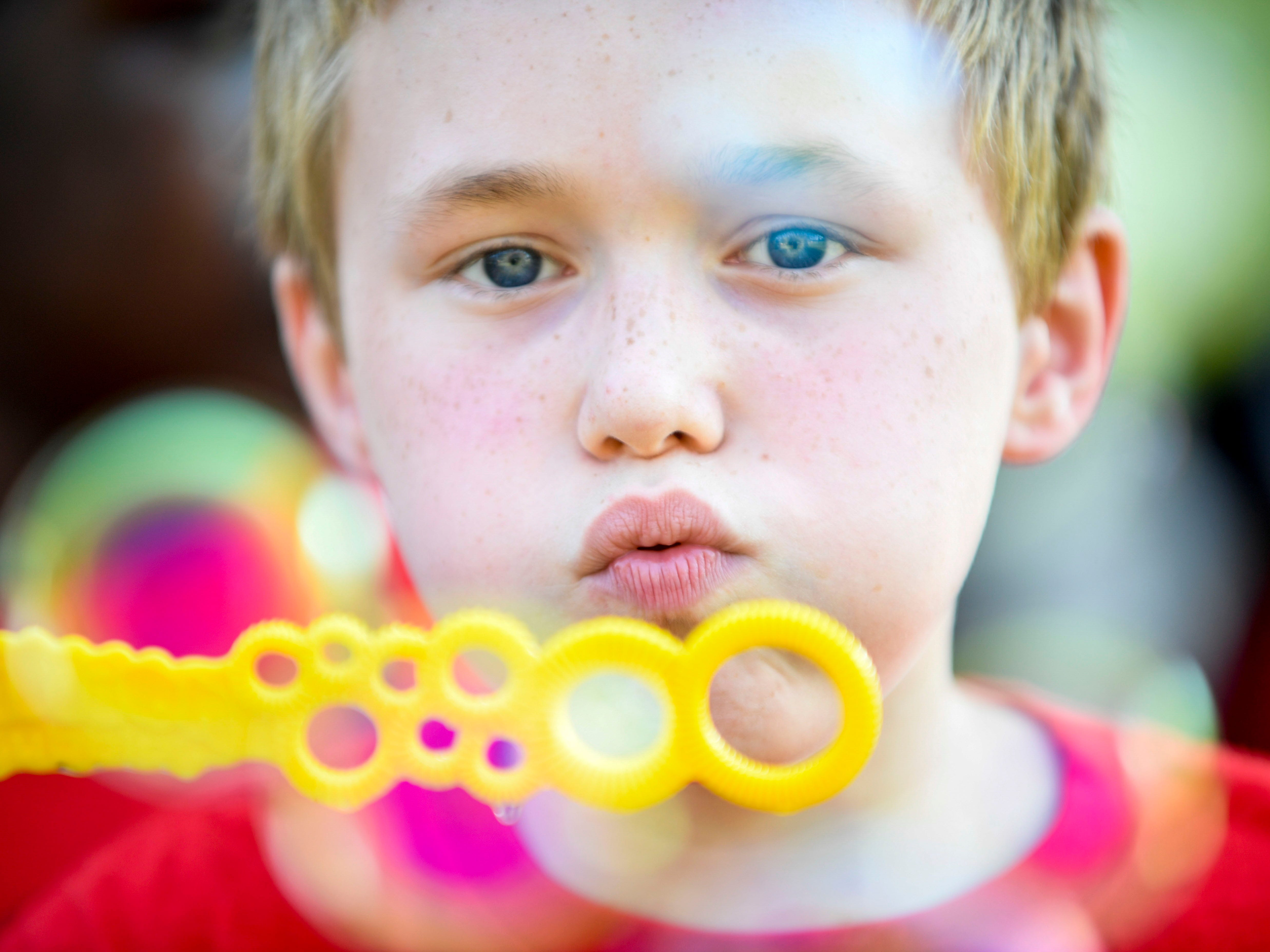A young boy blows bubbles at an activity station at the Day of Champions celebration held at Jackson Fairgrounds Park in Jackson, Tenn., on Wednesday, Sept. 19, 2018.