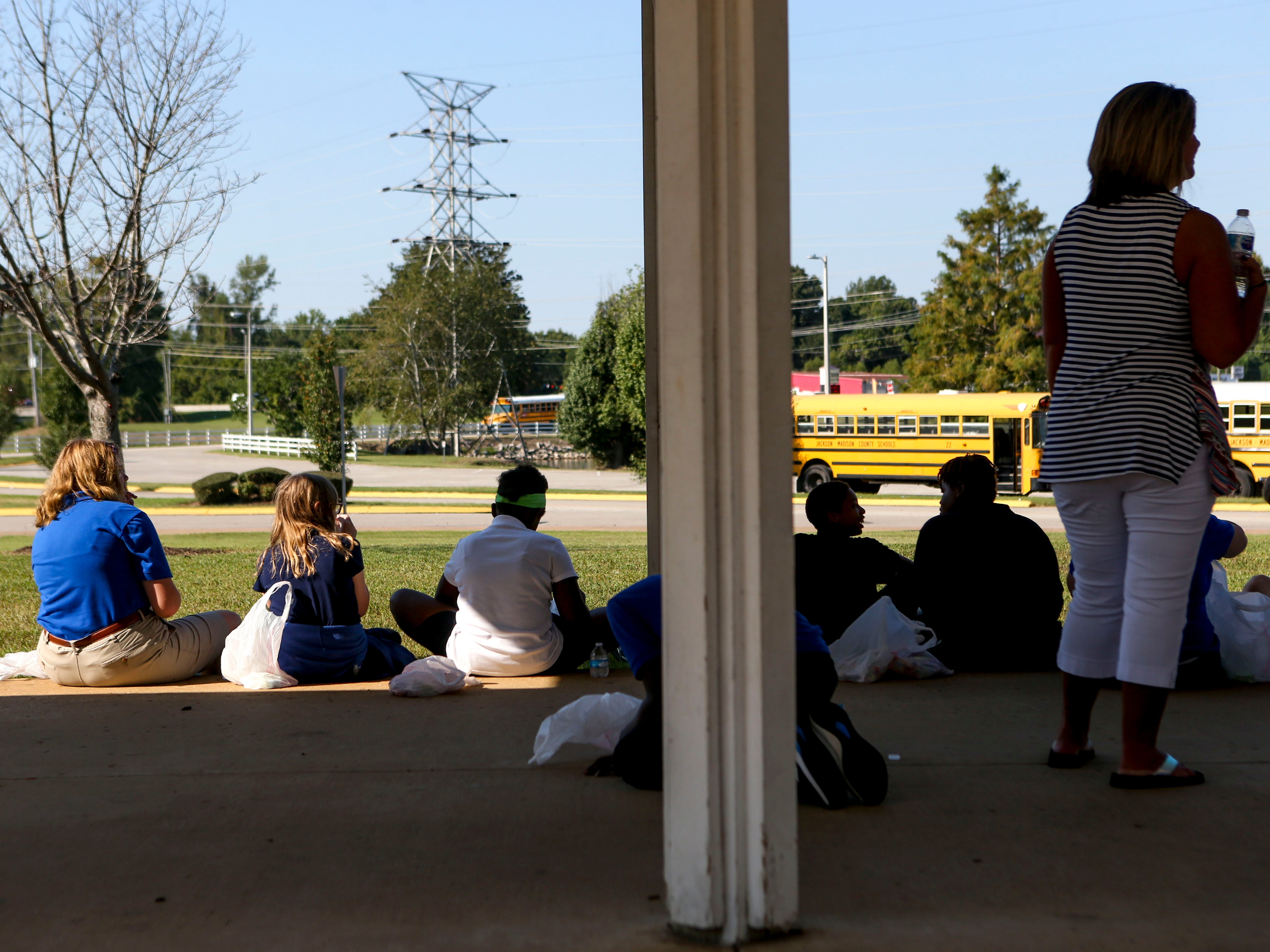 A group of attendees sits on a curb waiting for their bus to pick them up at the Day of Champions celebration held at Jackson Fairgrounds Park in Jackson, Tenn., on Wednesday, Sept. 19, 2018.