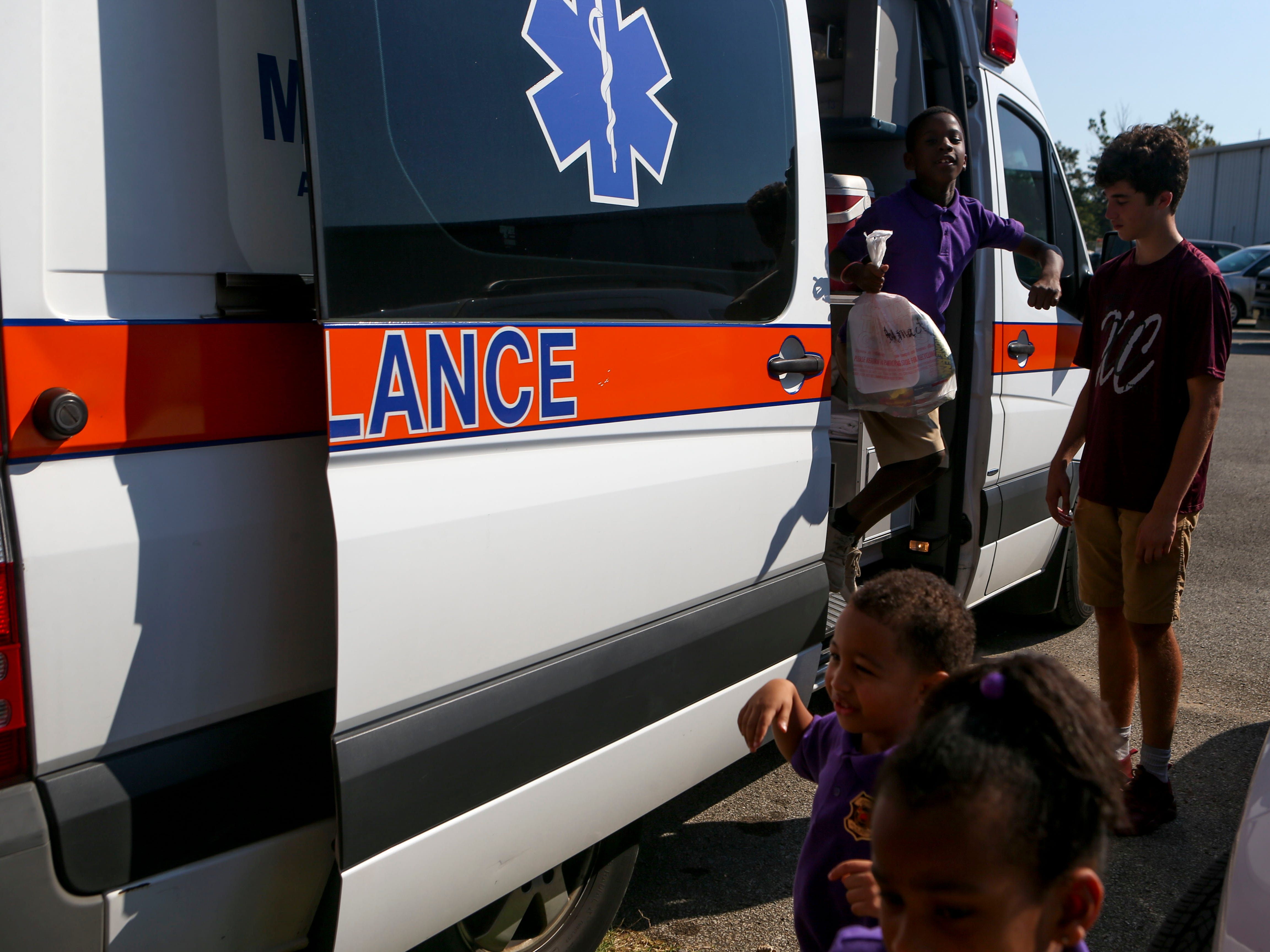 Kids exit an ambulance brought for them to explore at the Day of Champions celebration held at Jackson Fairgrounds Park in Jackson, Tenn., on Wednesday, Sept. 19, 2018.