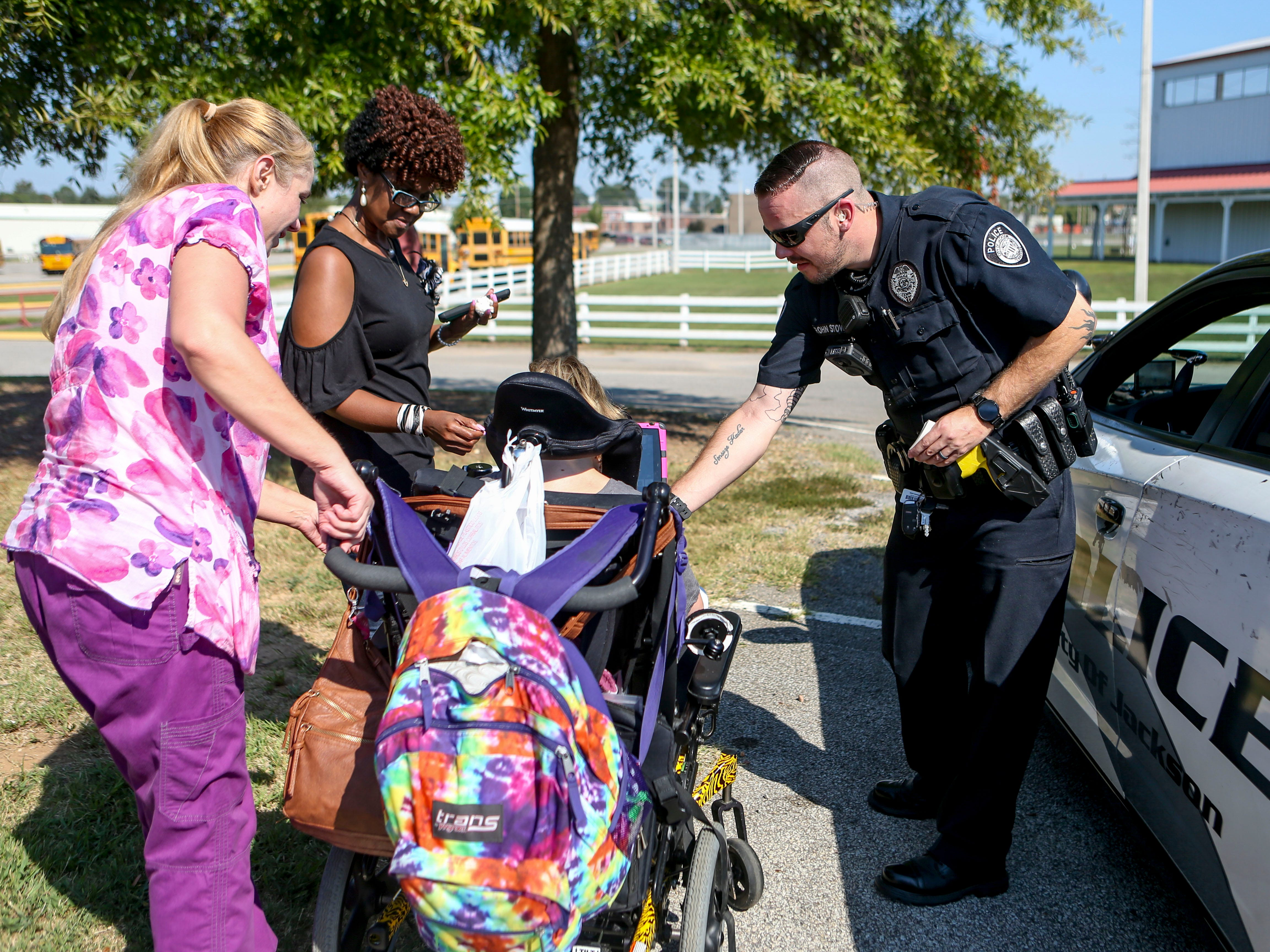 A Jackson Police Officer hands an attendee a sticker at the Day of Champions celebration held at Jackson Fairgrounds Park in Jackson, Tenn., on Wednesday, Sept. 19, 2018.