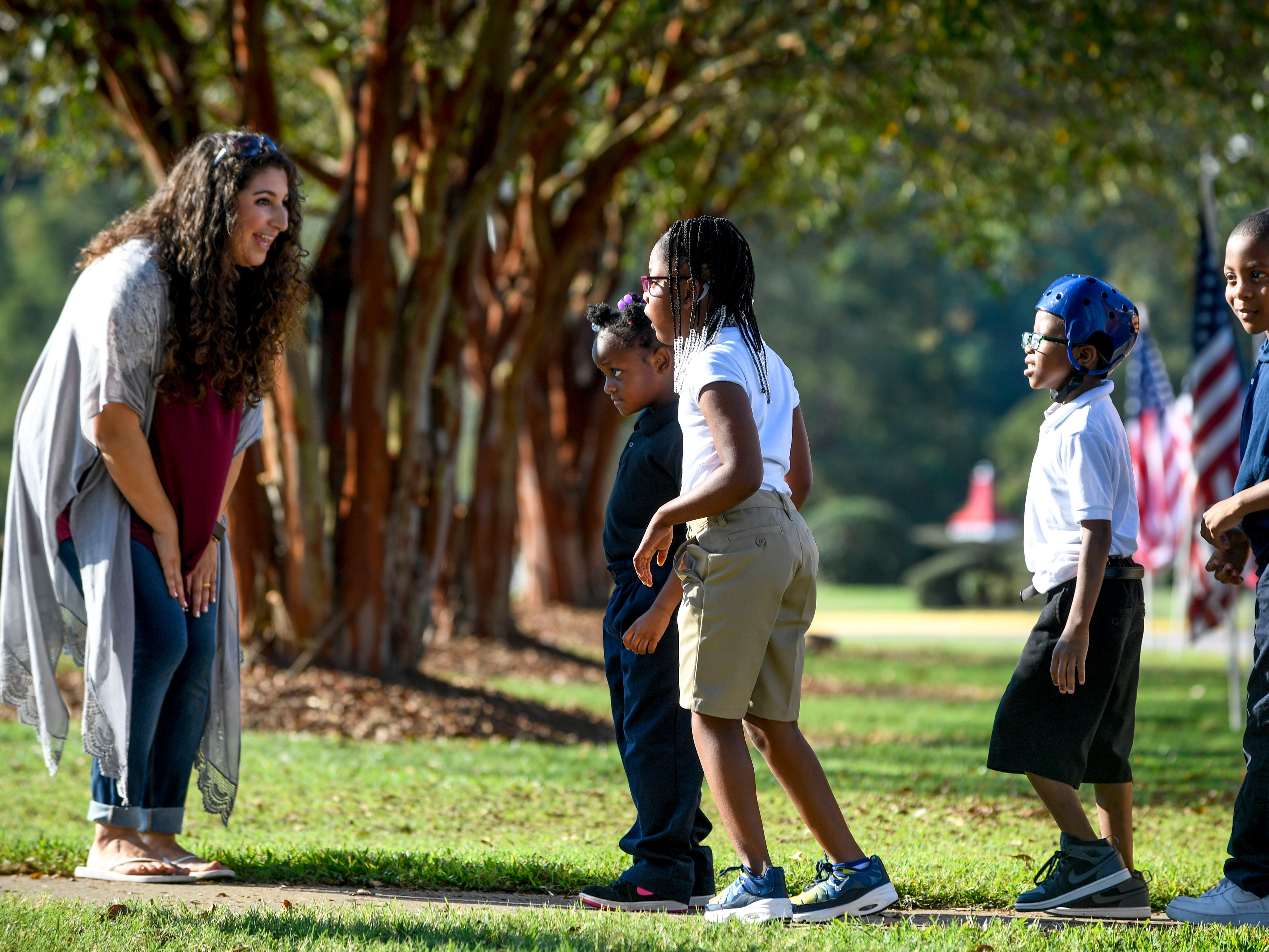 An organizer greets kids arriving from a bus at the Day of Champions celebration held at Jackson Fairgrounds Park in Jackson, Tenn., on Wednesday, Sept. 19, 2018.