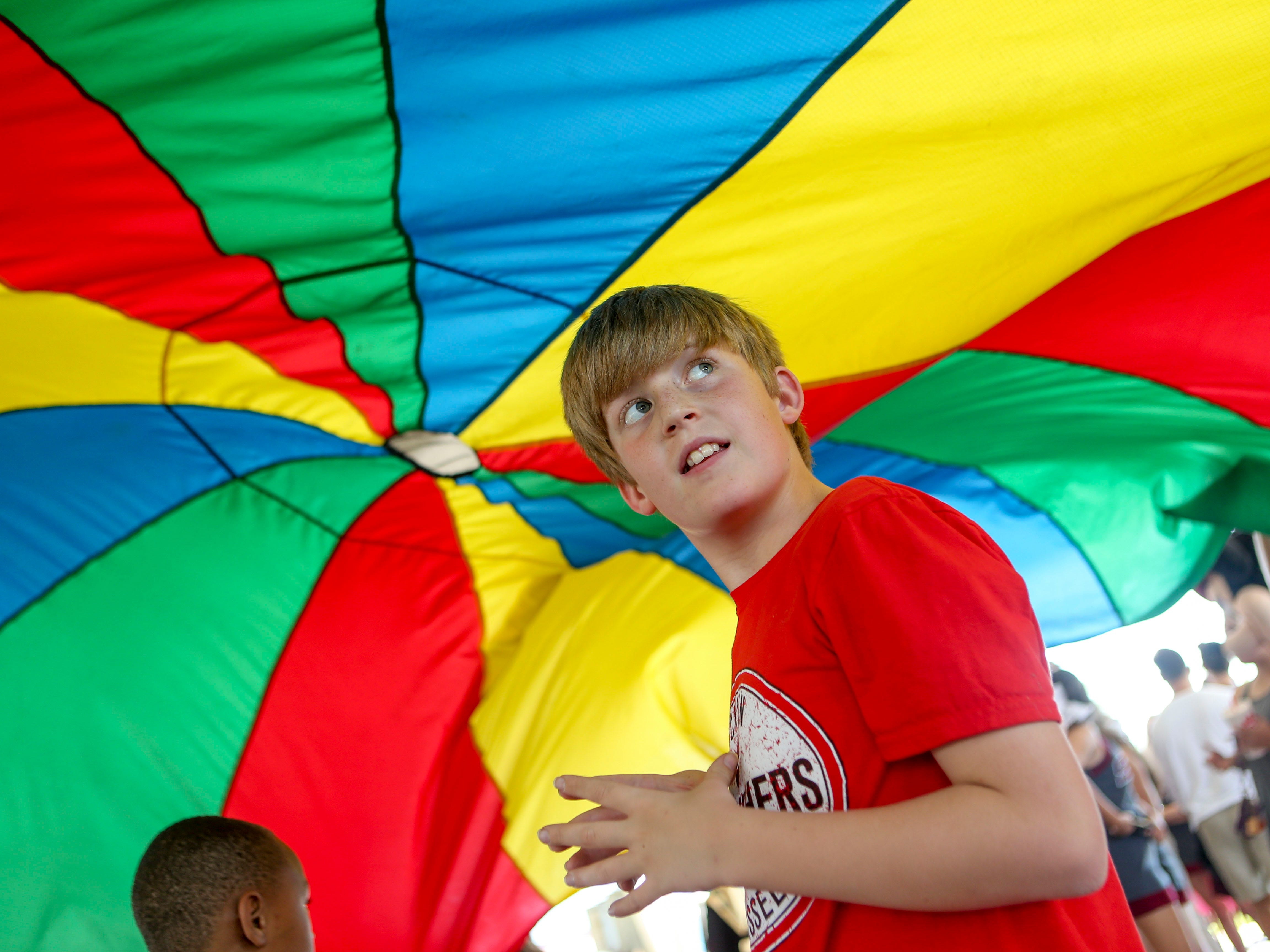 A boy looks around at people tossing a large tarp over his head at the Day of Champions celebration held at Jackson Fairgrounds Park in Jackson, Tenn., on Wednesday, Sept. 19, 2018.