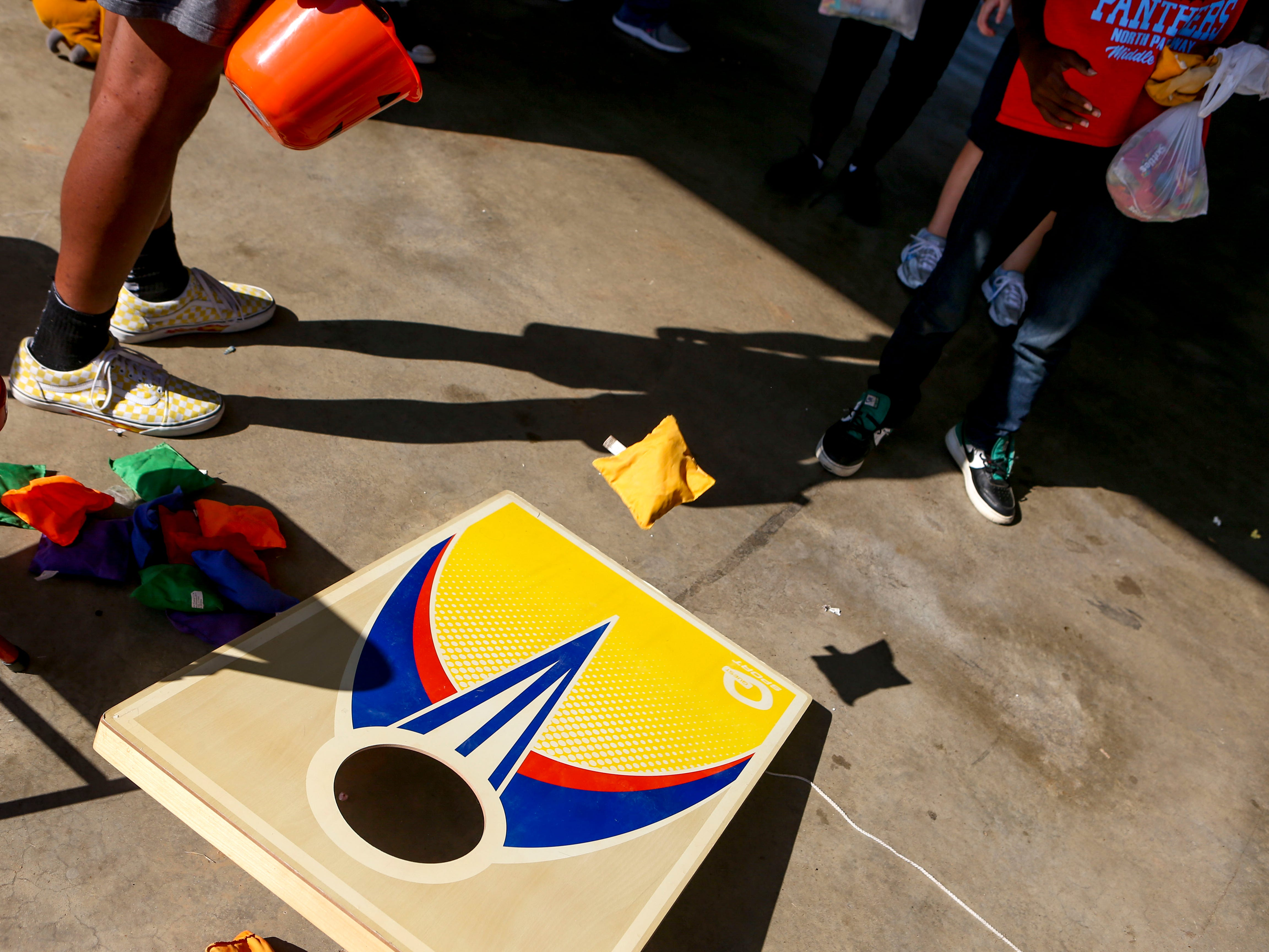 Kids attempt to toss a bean bag into a corn hole at the Day of Champions celebration held at Jackson Fairgrounds Park in Jackson, Tenn., on Wednesday, Sept. 19, 2018.