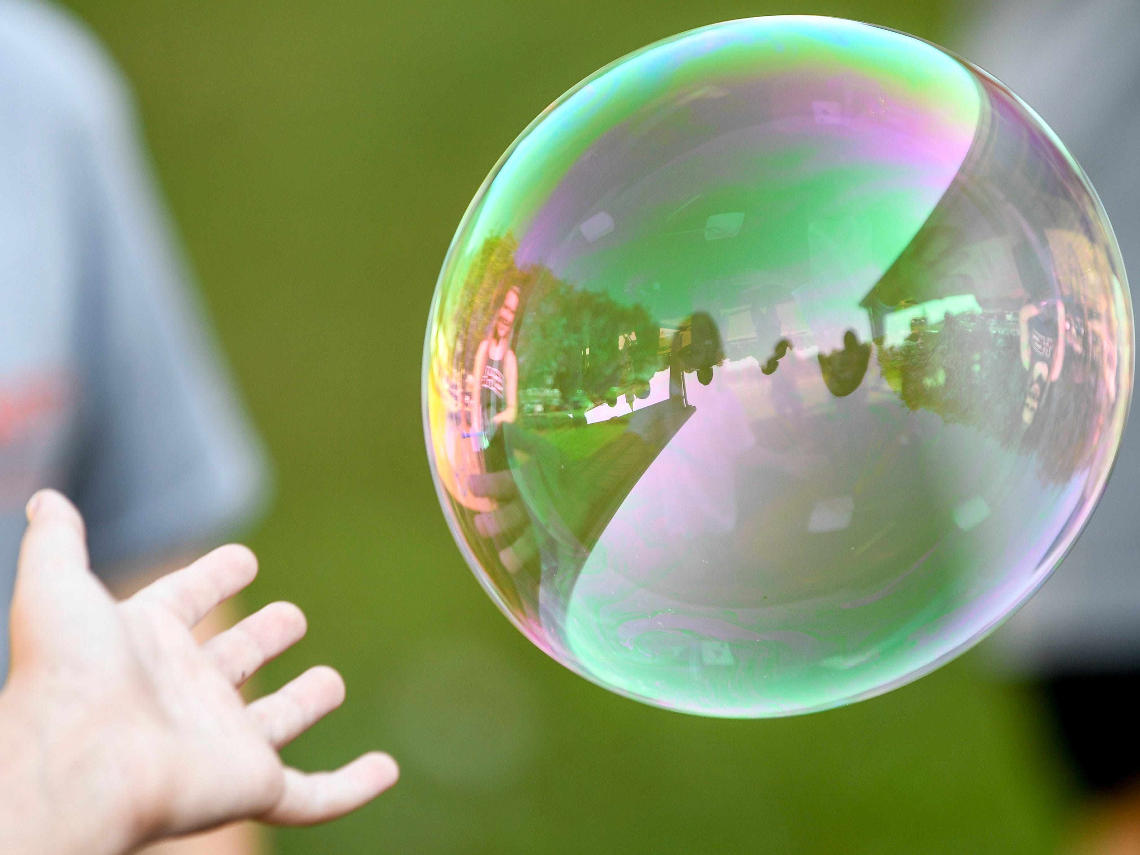 A young girl reaches to pop a bubble at the Day of Champions celebration held at Jackson Fairgrounds Park in Jackson, Tenn., on Wednesday, Sept. 19, 2018.