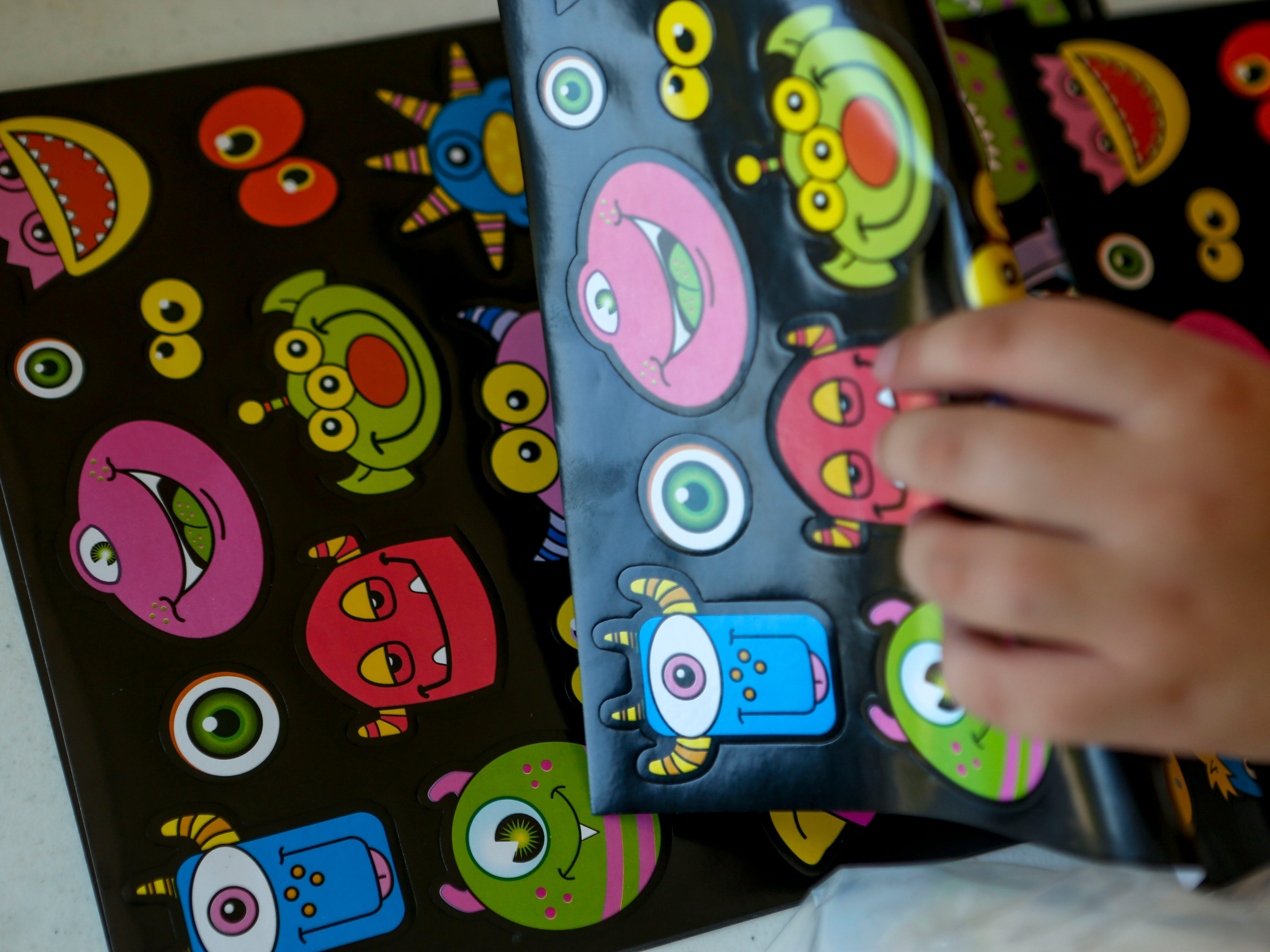A girl grabs a set of stickers to decorate a pan at the Day of Champions celebration held at Jackson Fairgrounds Park in Jackson, Tenn., on Wednesday, Sept. 19, 2018.