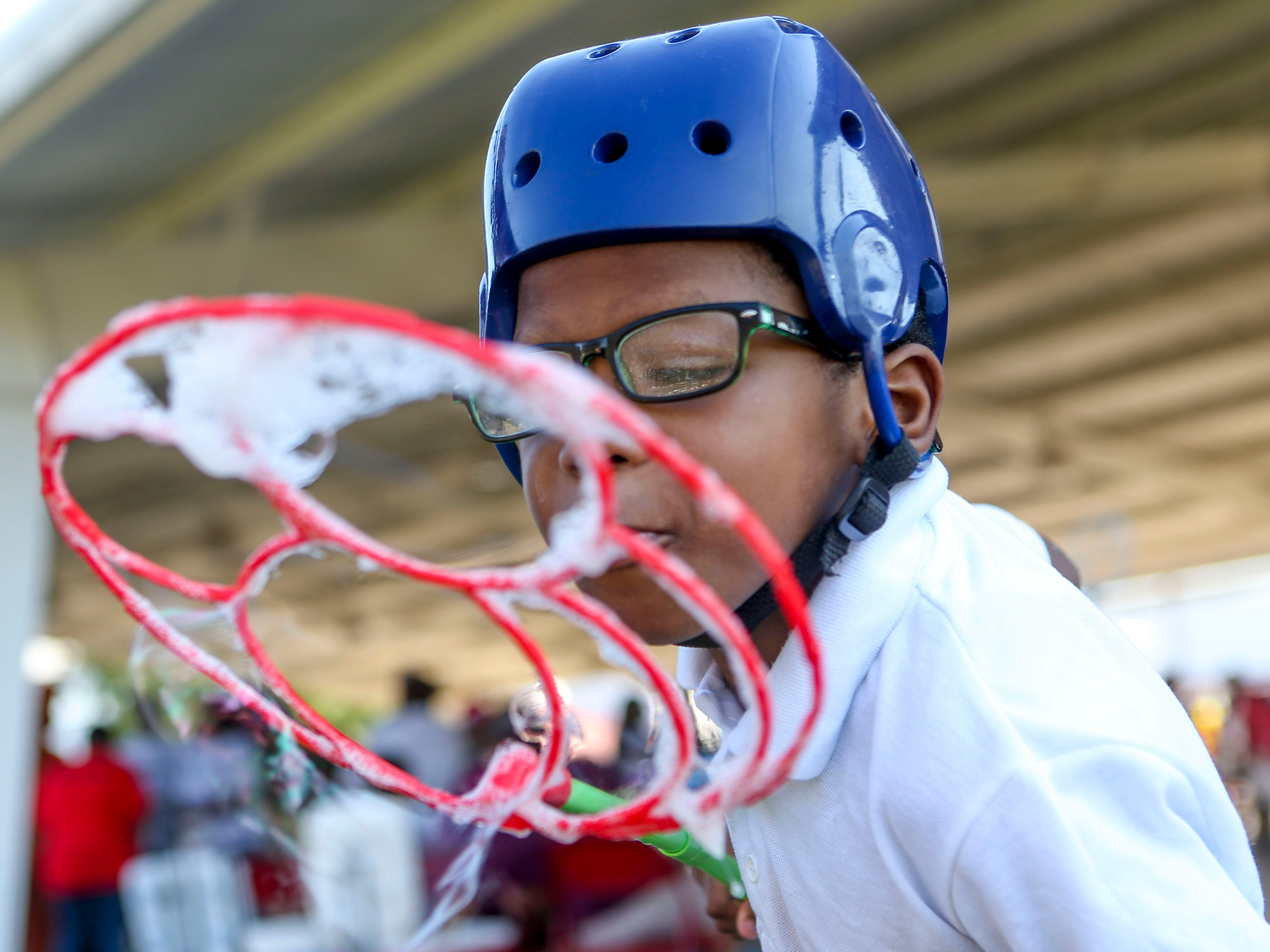 A young boy blows bubbles at the Day of Champions celebration held at Jackson Fairgrounds Park in Jackson, Tenn., on Wednesday, Sept. 19, 2018.