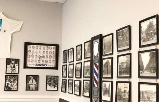 Customers at Crossroads Barbershop can sit and chat or look at the collection of photos on the walls while they wait.