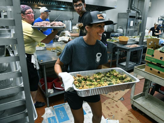tobi ragon a world central kitchen volunteer moves hot food at their relief operation in wilmington wednesday september 19 2018 - World Central Kitchen
