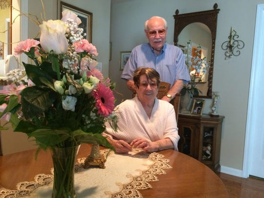 Leon and Emily Cagle pose by the flowers Leon recently sent to his bride.