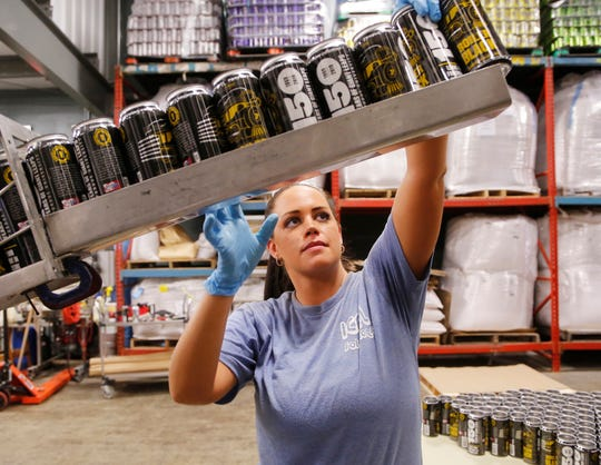 Heidi McIntire feeds cans into the canning for Boiler Black American Black Ale Wednesday, September 19, 2018, at People's Brewing Company, 2006 N. 9th Street in Lafayette. Boiler Black is Purdue University's second sanctioned signature beer produced by People's, following Boiler Gold. Boiler Black is an American style porter and will be available for Purdue's Homecoming this weekend.