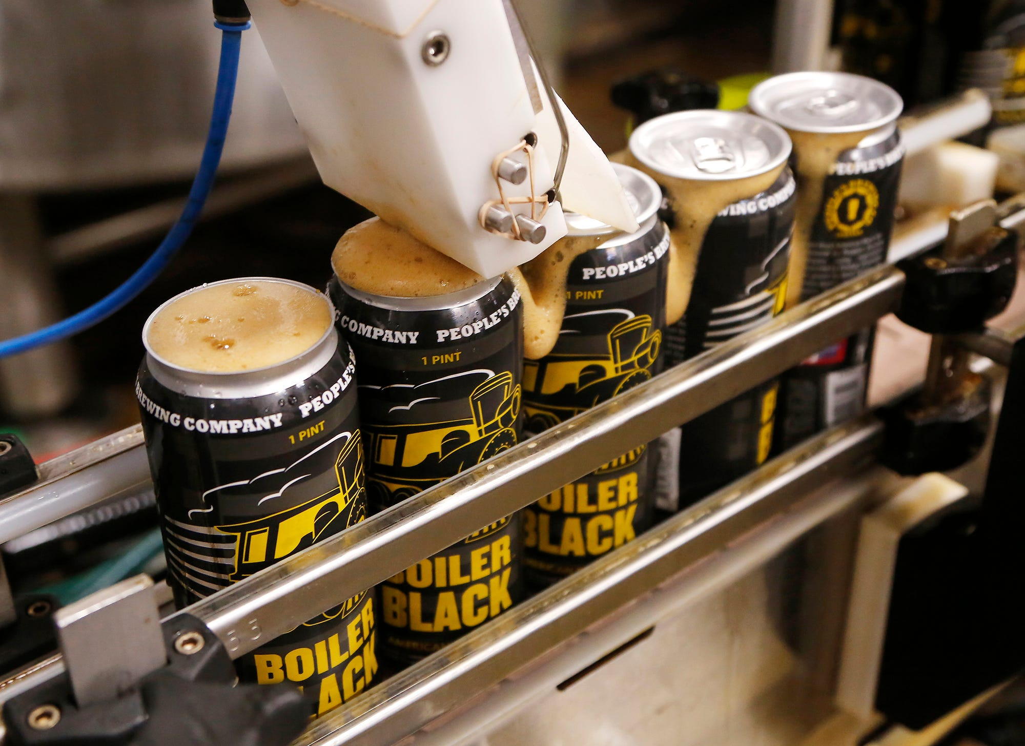 Boiler Black American Black Ale rolls off the canning line Wednesday, September 19, 2018, at People's Brewing Company, 2006 N. 9th Street in Lafayette. Boiler Black is Purdue University's second sanctioned signature beer produced by People's, following Boiler Gold. Boiler Black is an American style porter and will be available for Purdue's Homecoming this weekend.