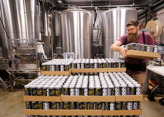 Troy Kult stacks a pallet with cases of Boiler Black American Black Ale as the beer comes off the canning line Wednesday, September 19, 2018, at People's Brewing Company, 2006 N. 9th Street in Lafayette. Boiler Black is Purdue University's second sanctioned signature beer produced by People's, following Boiler Gold. Boiler Black is an American style porter and will be available for Purdue's Homecoming this weekend.
