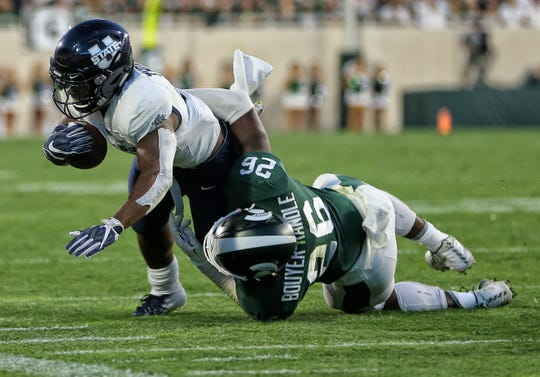Michigan State linebacker Brandon Bouyer-Randle brings down Utah State running back Darwin Thompson during the Spartans' opener on Aug. 31. Bouyer-Randle added Bouyer to his last name again to honor his mother, grandfather and their Lansing athletic legacy.
