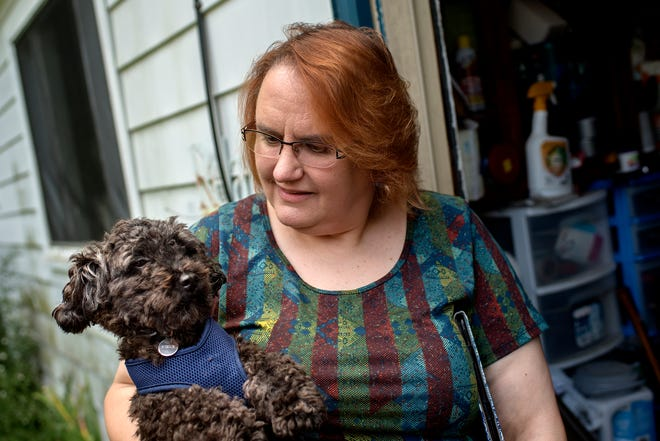 Animal Placement Bureau's Lisa Wallace holds her former foster dog Simon during a visit on Thursday, Sept. 13, 2018, at her home in Lansing. Wallace has been a foster parent to more than 200 dogs. The Animal Placement Bureau is a nonprofit, volunteer group that works to get area dogs placed in foster home and eventually adopted.