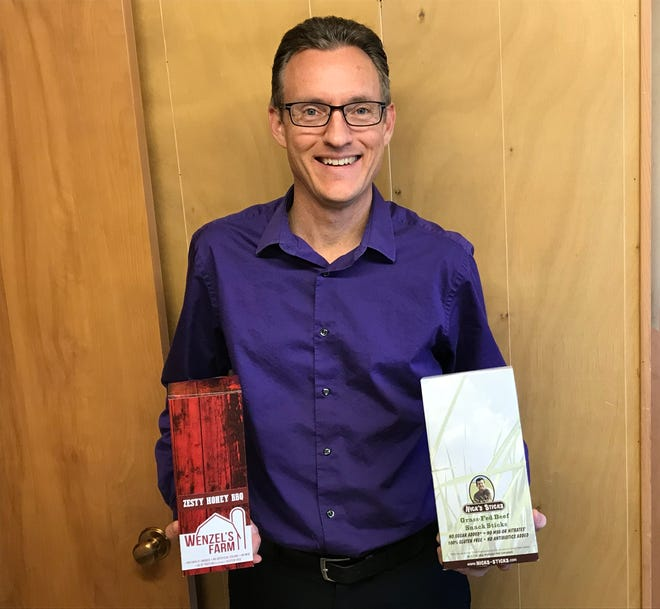 President of Wenzel's Farm Mark Vieth holds a box of Zesty Spicy BBQ snack sticks and grassfed Nick's Sticks inside his office.