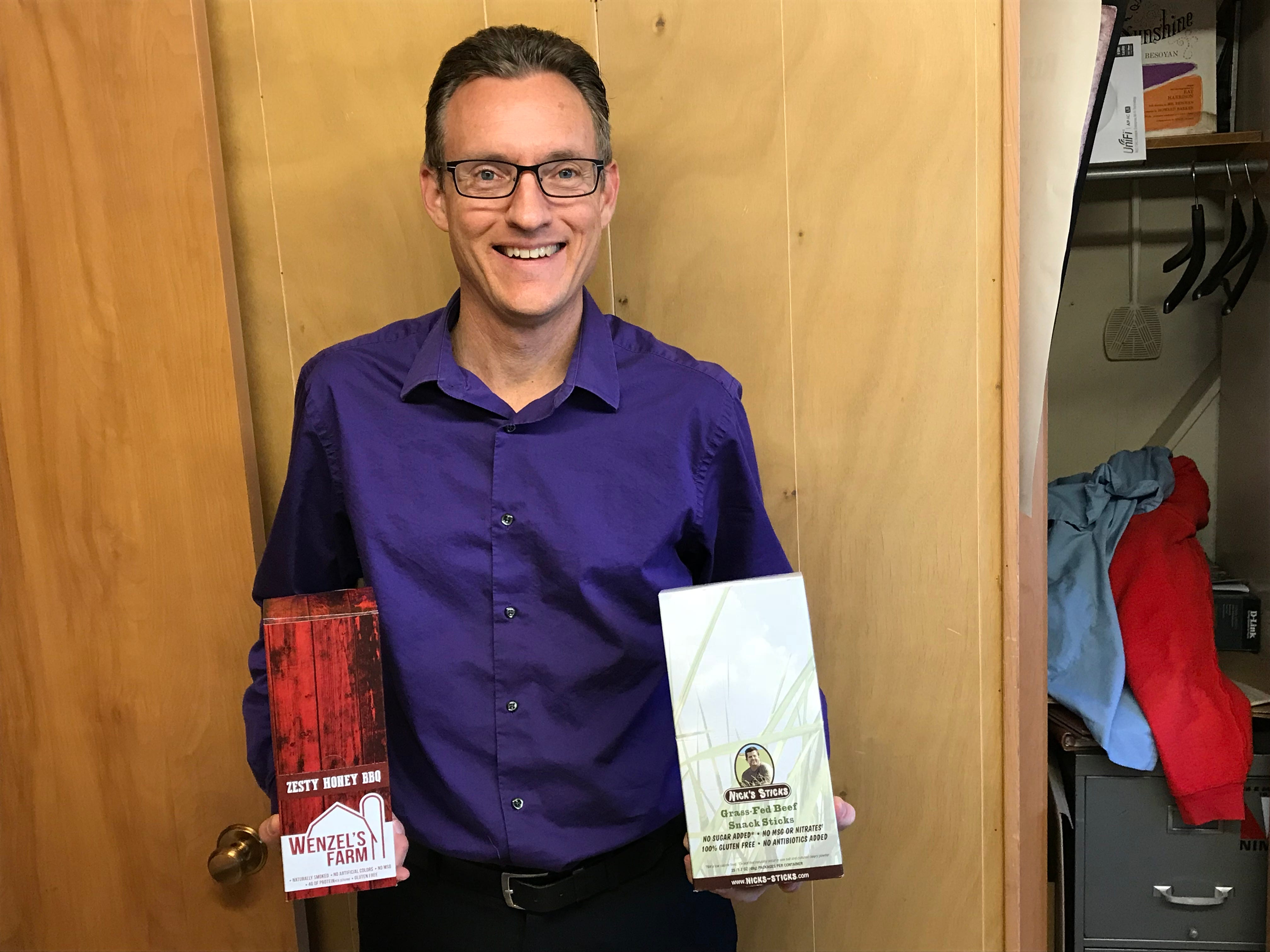 President of Wenzel's Farm president Mark Vieth holds a box of Zesty Spicy BBQ snack sticks and organic Nick's Sticks inside his office.