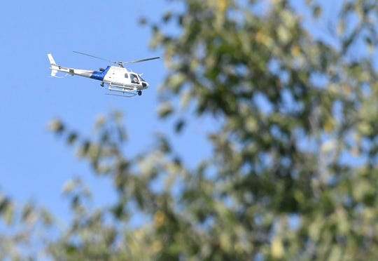 A helicopter flies above the Woodville Road area Wednesday afternoon as the hunt for Shawn Christy continues.