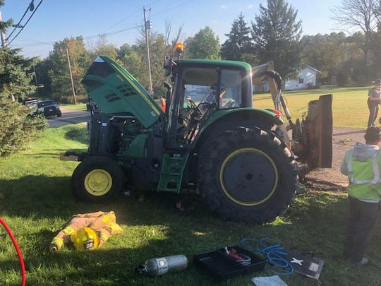 This is the scene Tuesday on Reed Road where a Mifflin Township road superintendent became trapped beneath the mower and was rescued.