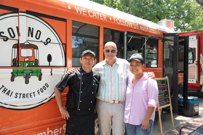 Tim Vimmonimit and Mai Mitrakul pose for a photo with Andrew Zimmern in front of their food truck Soi Number 9, as seen on Big Food Truck Tip, Season 1.