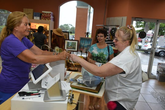 Volunteer Kimberly Porter completes a sale to Melody Brannan. The Bargain Basket, a mission of United Church of Marco Island, has paid off all indebtedness on the property through their sales of used clothes and home goods.