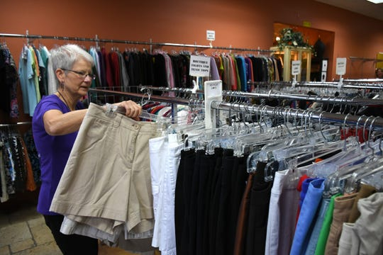 Volunteer Susan Koslowski stocks the shelves. The Bargain Basket, a mission of United Church of Marco Island, has paid off all indebtedness on the property through their sales of used clothes and home goods.