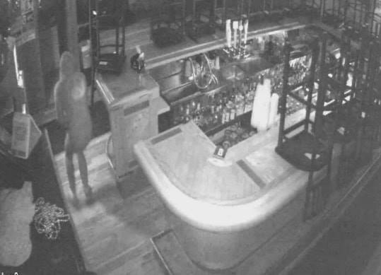 A surveillance photo shows a burglary suspect walking around a bar after hours in Okauchee.