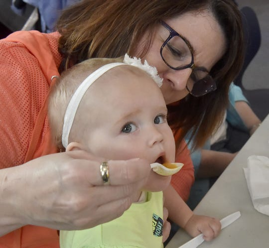 Paula Kintopf of New Franken helps her 11-month-old granddaughter, Adeline Boland, try booyah at the annual Booyah and Bread fund-raiser luncheon last April at the Belgian Heritage Center in Namur.
