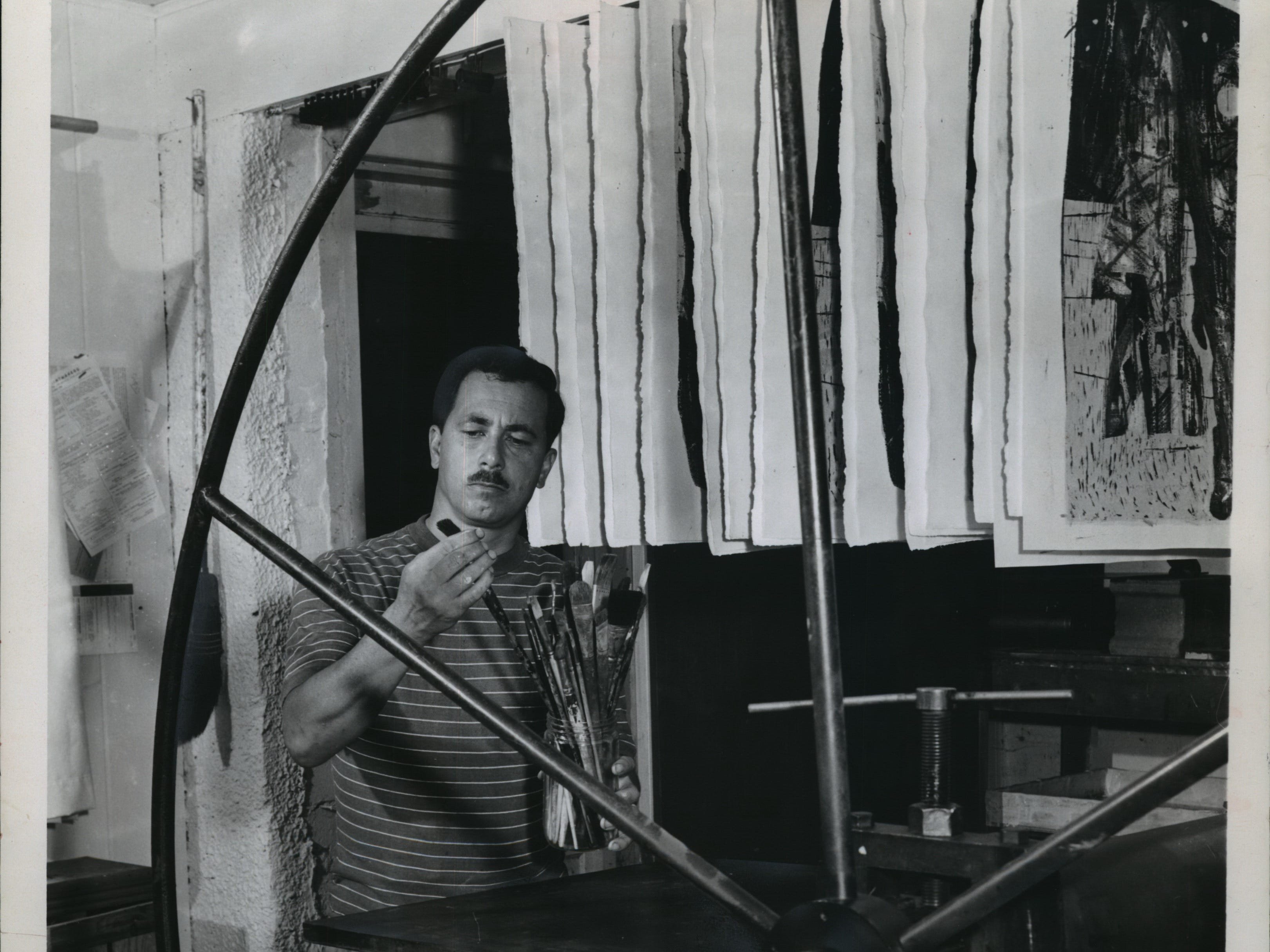 1960: In his Madison studio, Warrington Colescott stands behind and looks surrounded by the large wheel of his intaglio printing press.