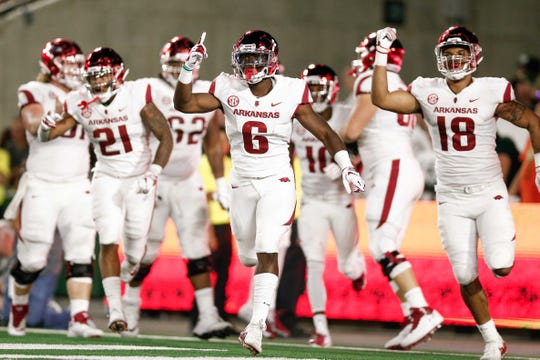 Arkansas running back T.J. Hammonds (6) celebrates his touchdown with running back Devwah Whaley (21) and tight end Jeremy Patton (18) in the third quarter against Colorado State on Sept. 8, 2018, in Fort Collins, CO.