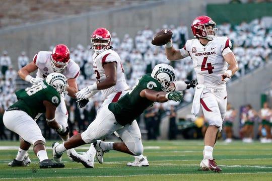 Arkansas quarterback Ty Storey (4) passes under pressure from Colorado State defensive end Emmanuel Jones (33) on Sept. 8, 2018, in Fort Collins, CO.