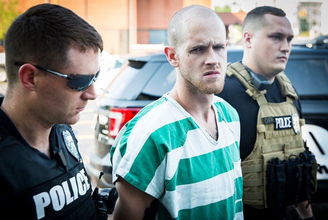 Brady Allen Turner, 25, is escorted to City Hall for questioning Wednesday afternoon after a more than two-day manhunt by city and county police. Madison County officers arrested Turner and he was returned to Delaware County.