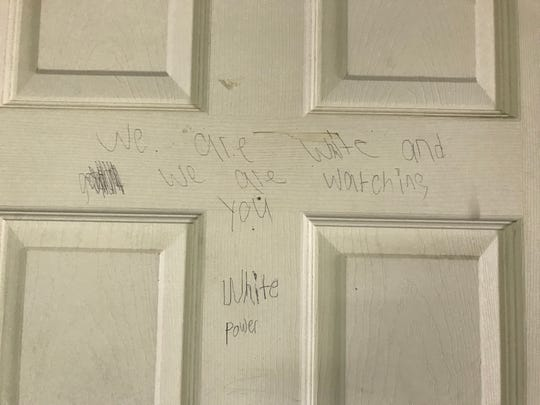 "Racist graffiti scrawled on a door at Walnut Grove Missionary Baptist Church in Murfreesboro by a group of vandals says ""we are white and we are watching you"" and ""white power."""