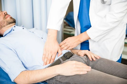 Doctor Examining Abdomen Of Patient
