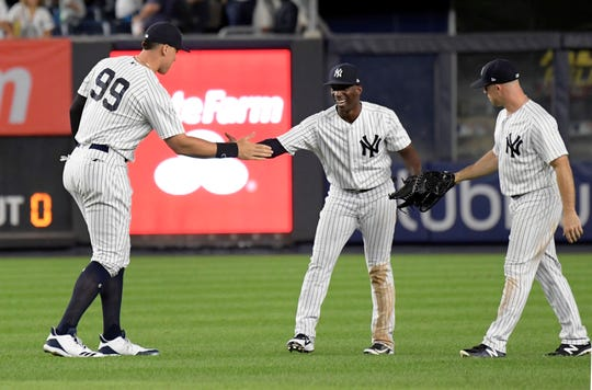 New York Yankees' Aaron Judge (99), Andrew McCutchen and Brett Gardner, right, celebrate after the Yankees defeated the Toronto Blue Jays 11-0 in a baseball game Friday, Sept.14, 2018, at Yankee Stadium in New York.