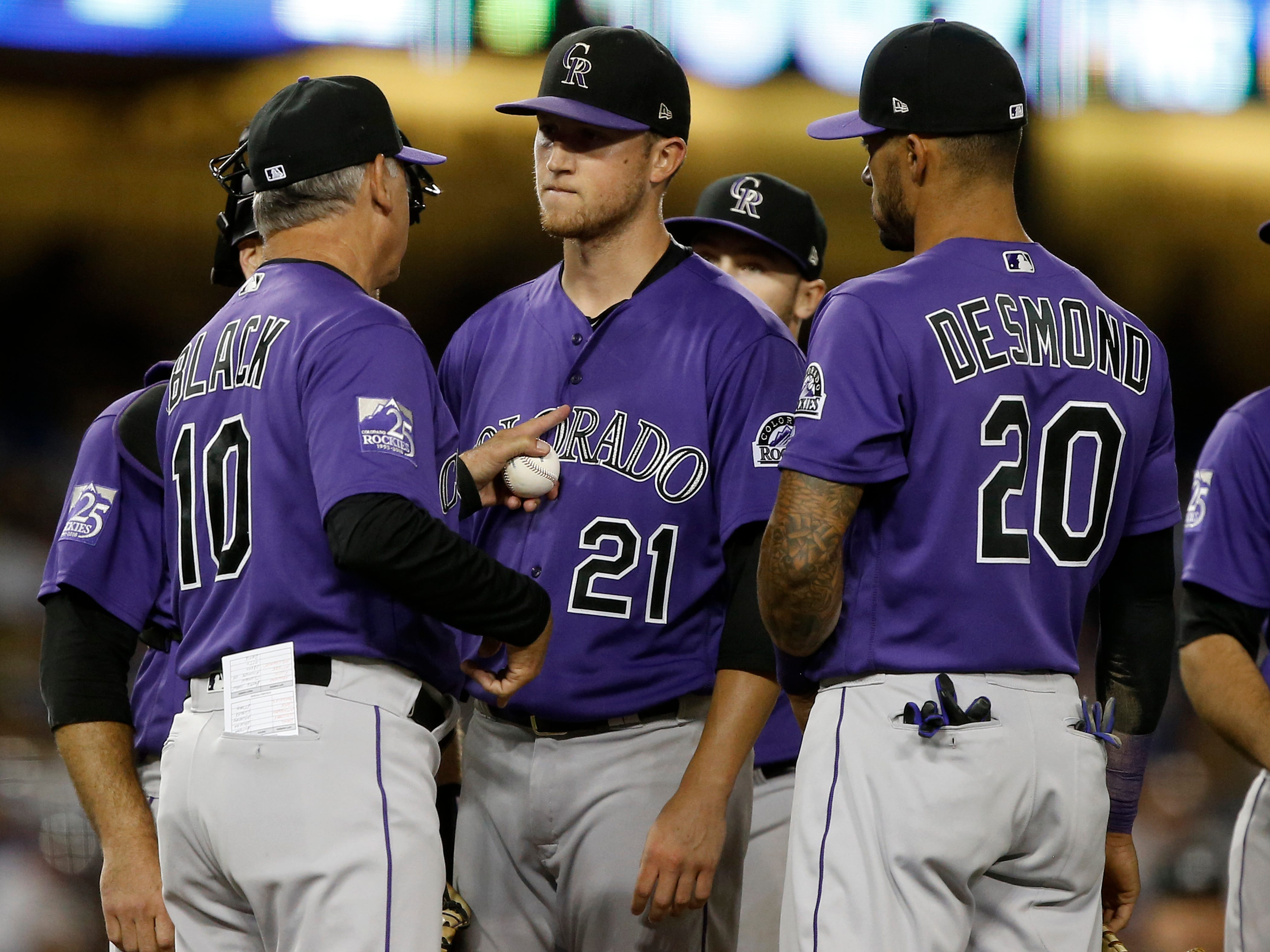 Colorado Rockies manager Bud Black, left, talks to starting pitcher Kyle Freeland (21), while switching pitchers, with first baseman Ian Desmond (20) looking on during the seventh inning of a baseball game against the Los Angeles Dodgers in Los Angeles, Tuesday, Sept. 18, 2018. (AP Photo/Alex Gallardo)